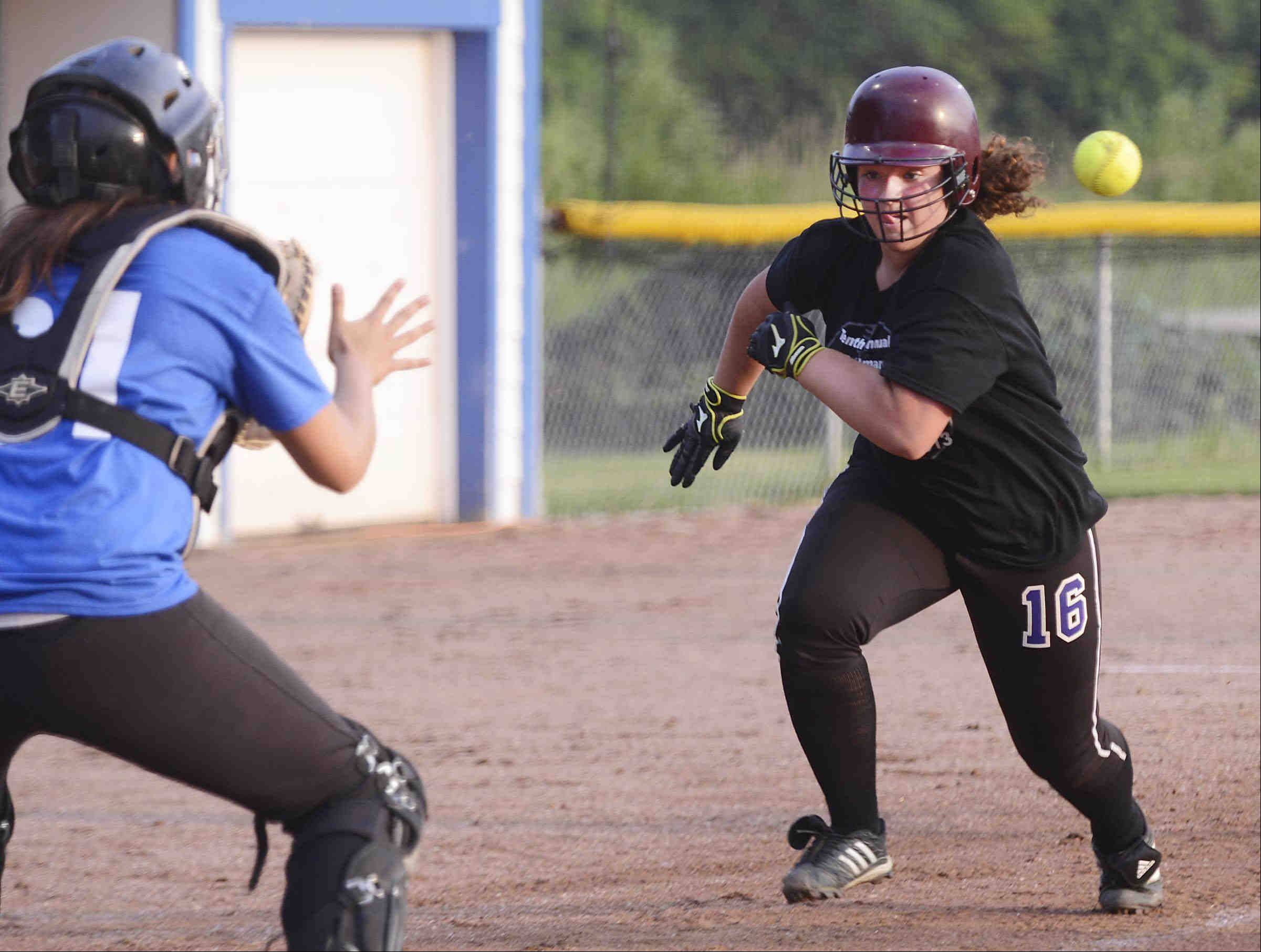 Caroline Sobeski charges toward catcher Sarah Leudo Monday during the Tenth Annual Fehlman Memorial Senior All-Star softball game at Judson University. Sobeski is an Elgin High School graduate and was playing for the East All Stars, while Leudo is a Cary-Grove High School grad playing for the West All Stars. Sobeski was tagged out on the throw from shortstop Kali Kossakowski of St. Edward.