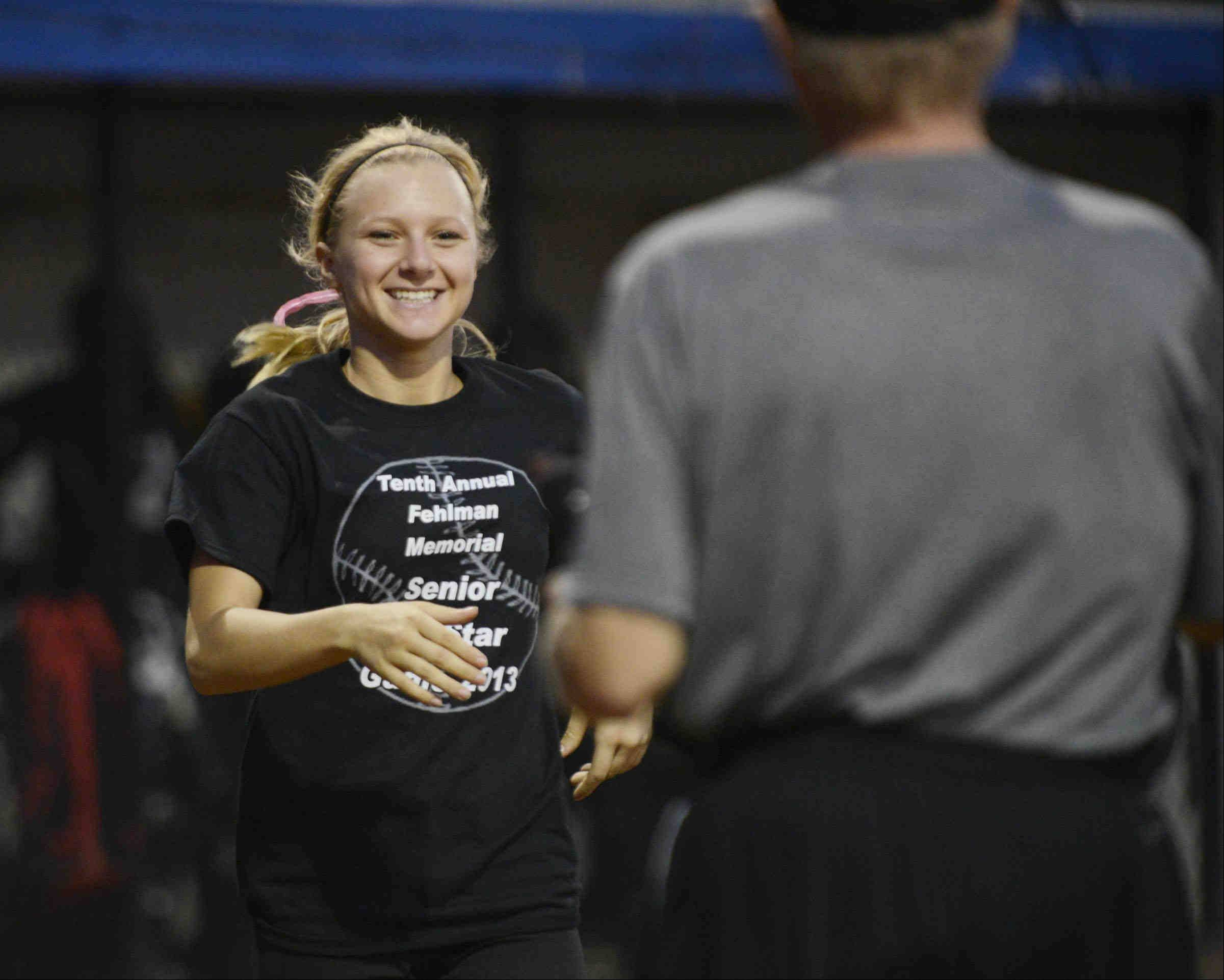 East All Star Rachel Odolski comes to accept her MVP trophy from Daily Herald Fox Valley Sports Editor John Radtke Monday after the Tenth Annual Fehlman Memorial Senior All-Star softball game at Judson University.