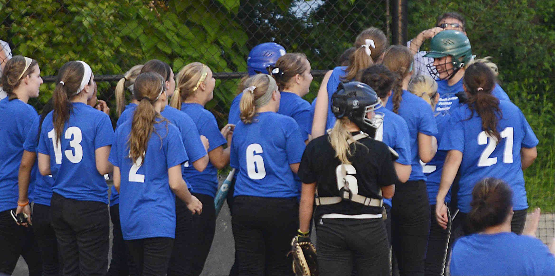 West All Star pitcher Kirsten Stevens of Prairie Ridge High School is greeted at home plate after her eighth inning home run Monday during the Tenth Annual Fehlman Memorial Senior All-Star softball game at Judson University.