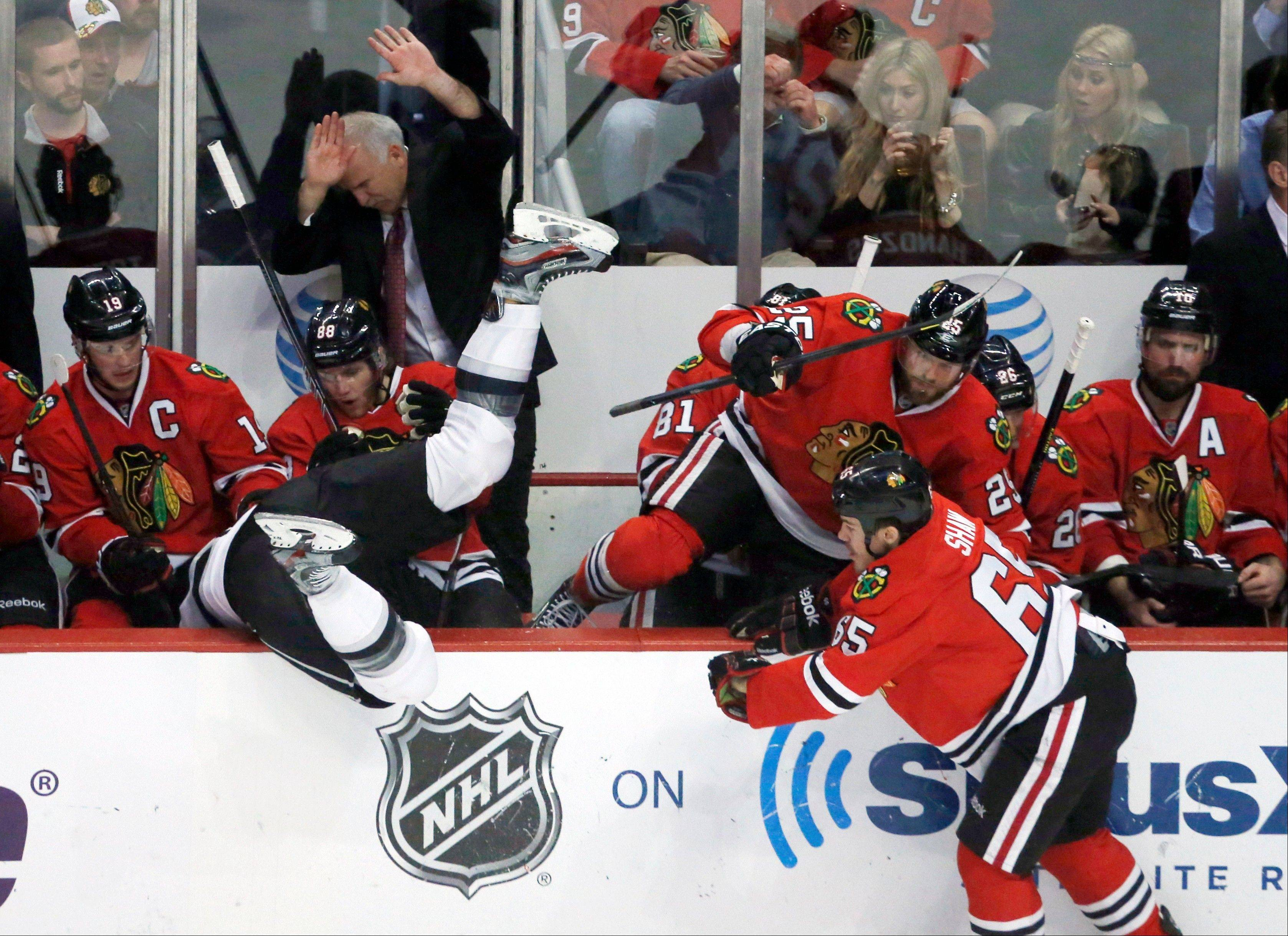 Patrick Shaw sends Kings defenseman Jake Muzzin into the Blackhawks bench during Game 5 of the Western Conference finals.