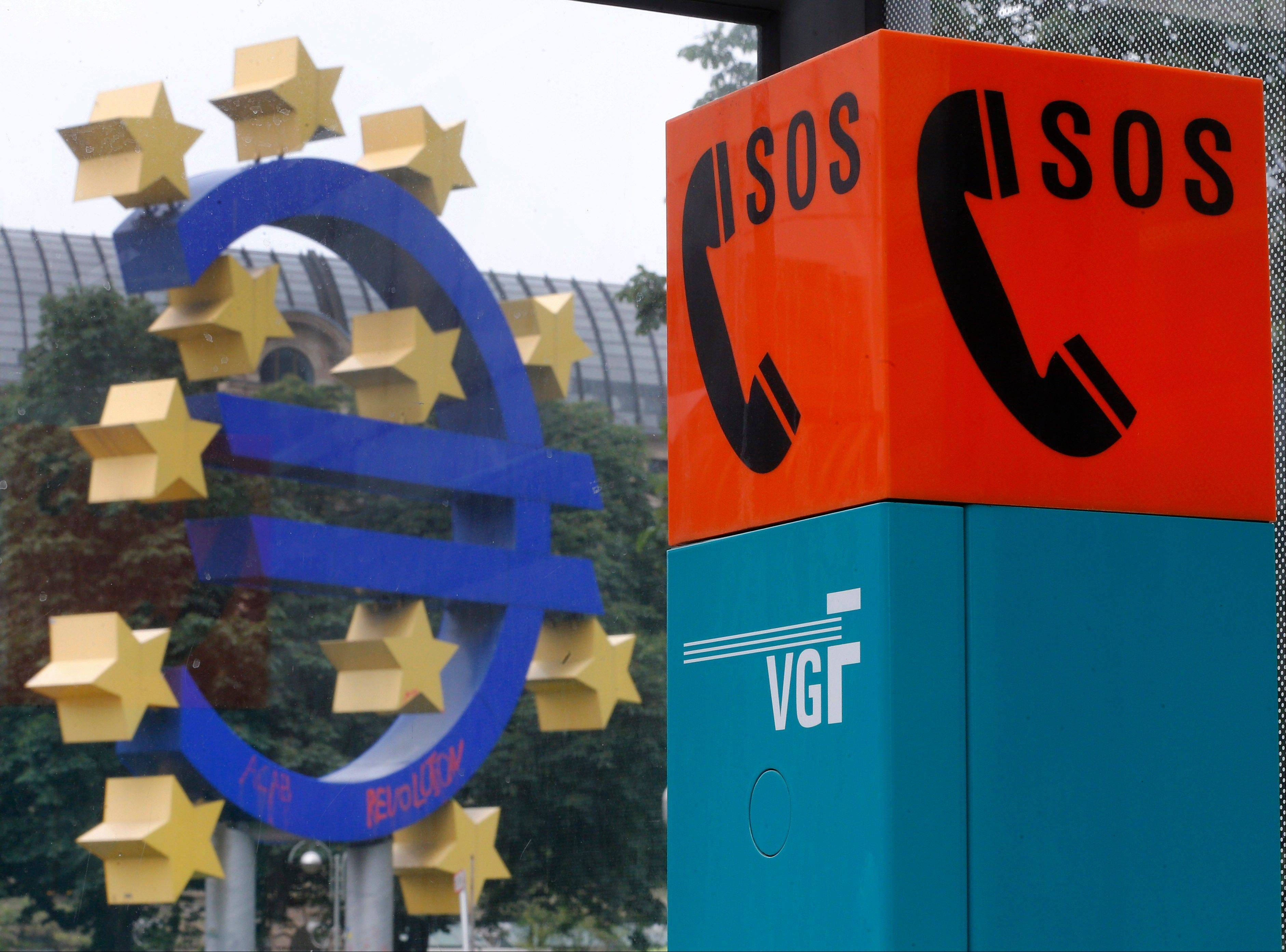 An emergency phone at a bus stop is pictured near the Euro sculpture in front of the European Central Bank, ECB, in Frankfurt, Germany, Tuesday. A key ECB program that has been credited with calming the 3�-year-old euro debt crisis faced a legal challenge Tuesday in Germany�s highest court.