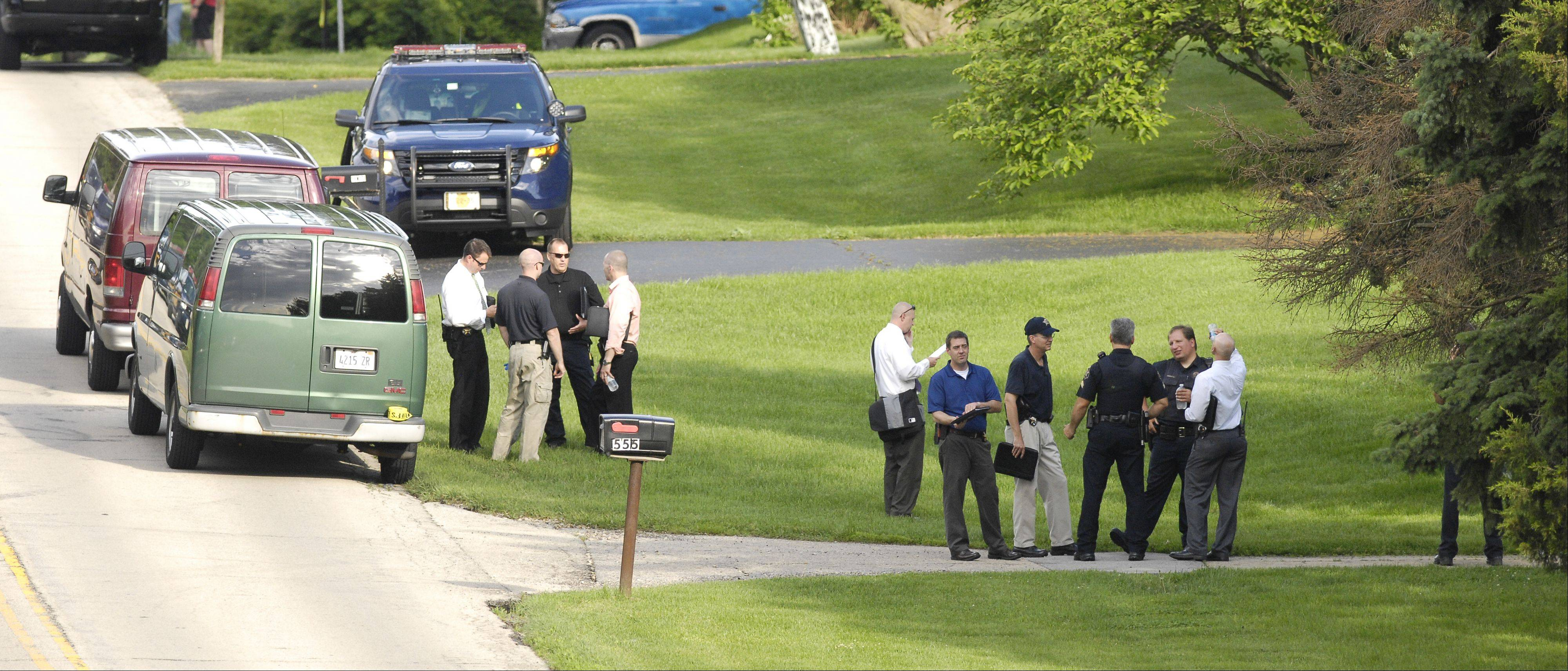 Police investigate Tuesday on Oldfield Road near Darien where four members of a family were found dead.