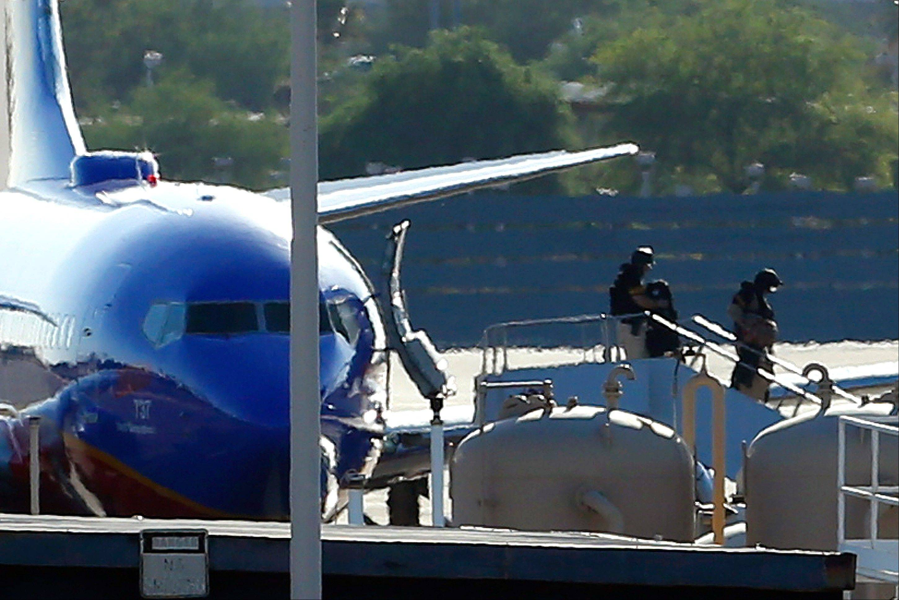 Members of the bomb squad walk off a Southwest Airlines plane on the ground at Phoenix Sky Harbor International Airport after the FBI says a �telephonic bomb threat� against a Southwest flight from Los Angeles to Texas led to the plane being diverted to Phoenix on Monday, June 10, 2013. Flight 2675 left Los Angeles International Airport at 2:12 p.m. and was heading to Austin before the threat was received by telephone. The plane landed safely at the Phoenix airport at about 3 p.m.