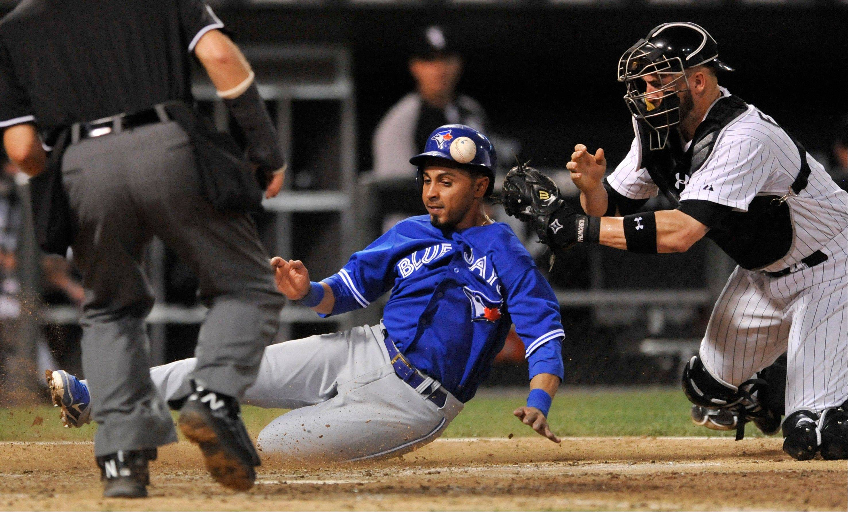 Maicer Izturis scores on a Munenori Kawasaki double as Tyler Flowers tries to apply the tag during the 10th inning of Toronto's victory over the White Sox on Tuesday at U.S. Cellular Field.