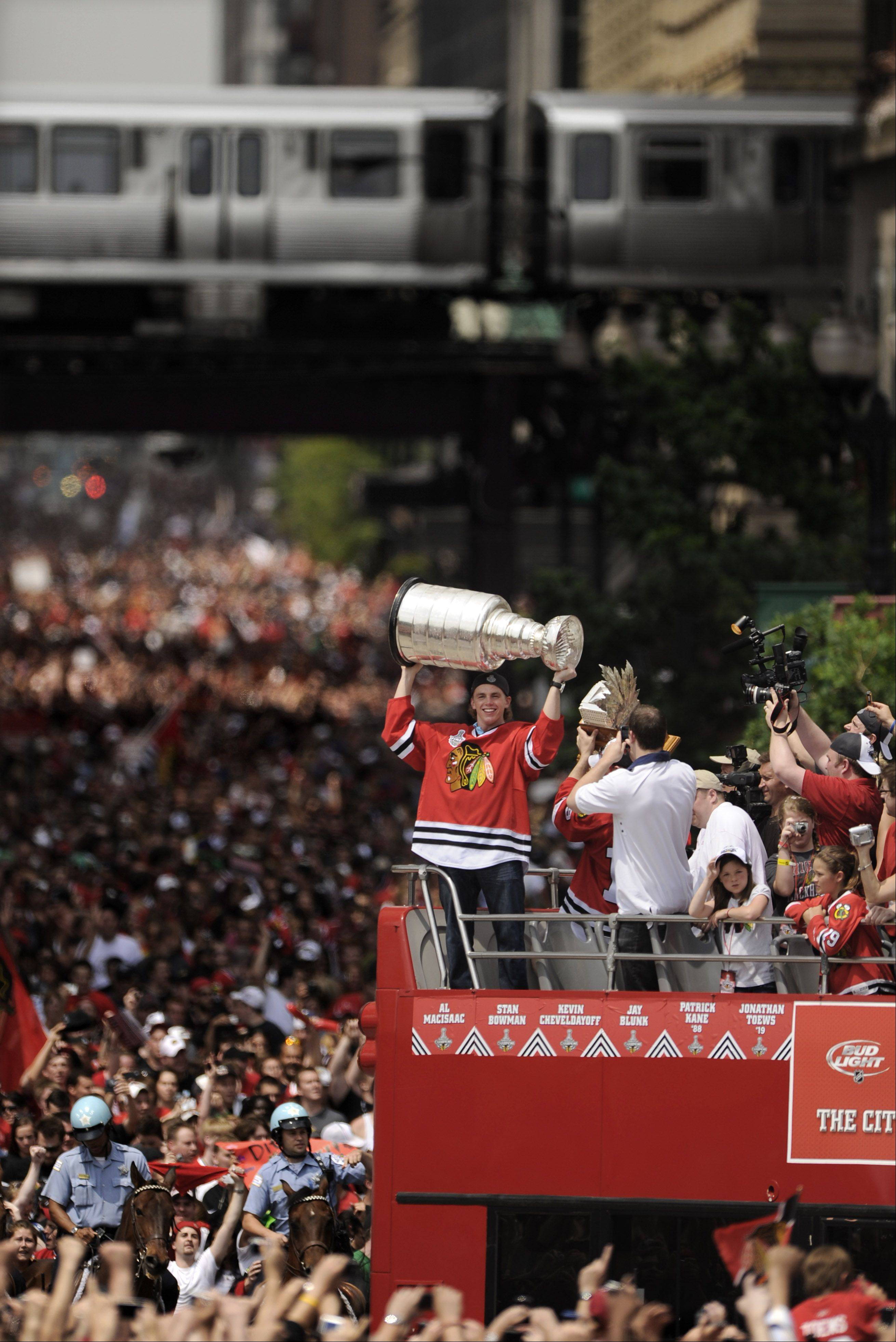 The Chicago Blackhawks� Patrick Kane hoists the Stanley Cup while celebrating with fans during a parade on Washington Street after the team�s cup win in 2010.