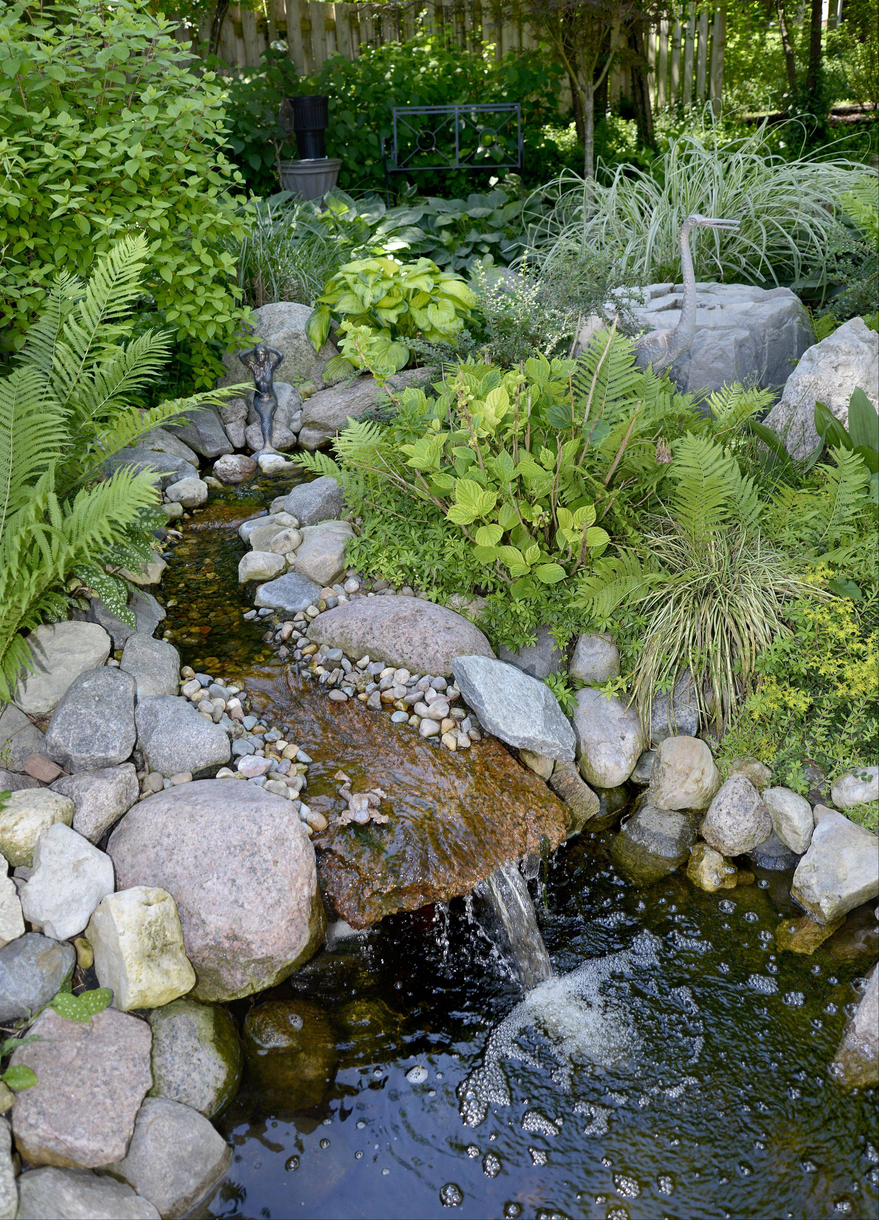 "A stream and koi pond highlight the back yard of Sandi and David Leeming's Batavia home. Their gardens will featured on the Batavia Plain Dirt Gardeners ""Gardens of De-Light and Shade"" garden walk on Saturday, June 22."