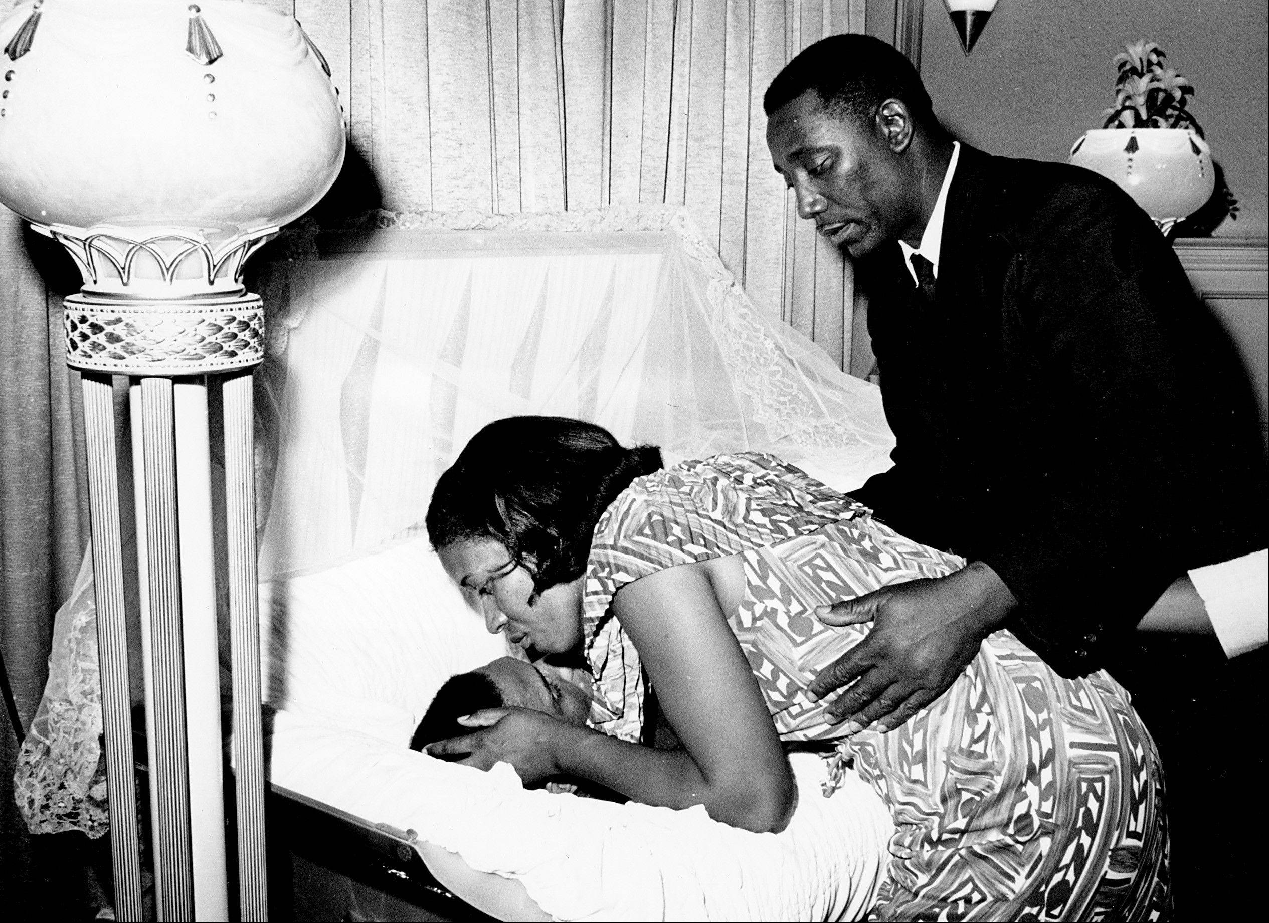 Myrlie Louise Evers, widow of civil rights activist Medgar Evers, leans down to kiss her late husband's forehead before the casket was opened for public viewing at a funeral home in Jackson, Miss. Evers, who was the first Mississippi field director of NAACP, 1954-1963, was 37 when he was assassinated outside the family's north Jackson home on June 12, 1963.