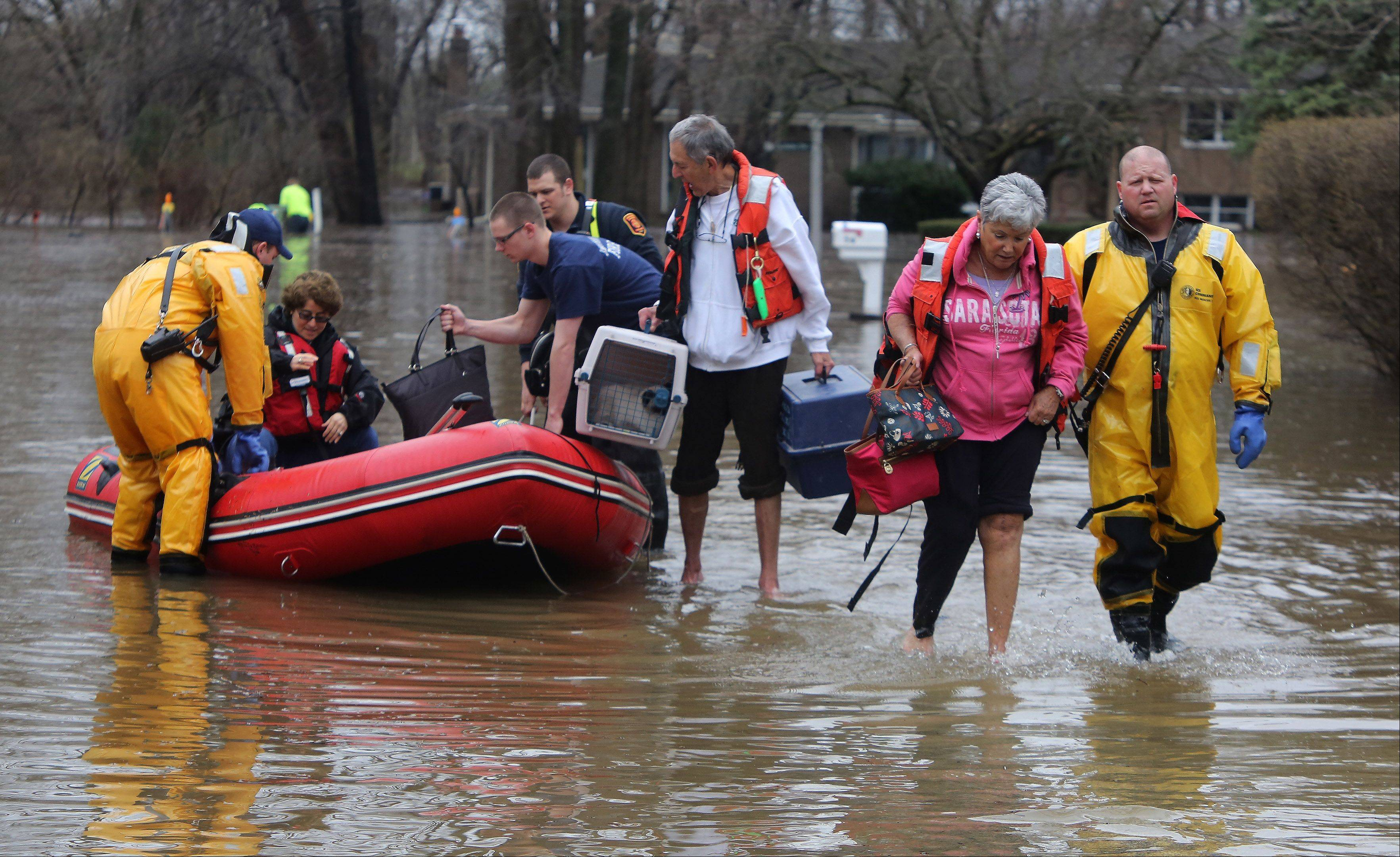 Firefighter Jason Stockton, of the Lincolnshire-Riverwoods Fire Department, helps resident Arlene Marshack, right, as other firefighters help her husband, Martin, and another homeowner, Wendy Kritt, along Lincolnshire Drive after flooding overwhelmed the neighborhood in Lincolnshire in April.