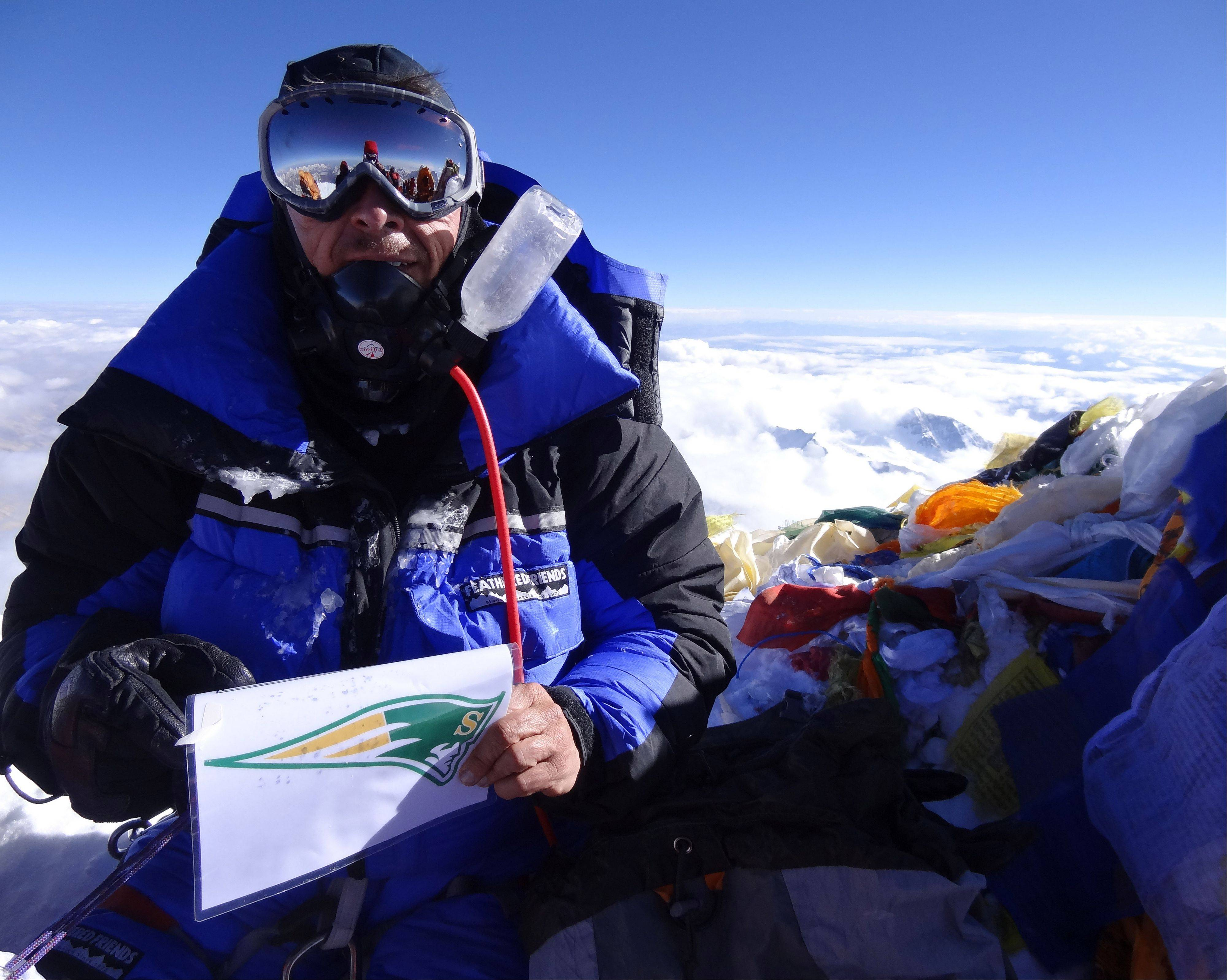 Stevenson High School graduate and Buffalo Grove native Dave Roskelley holds a laminated Stevenson High School sports logo sign which he left at the summit of Mount Everest.