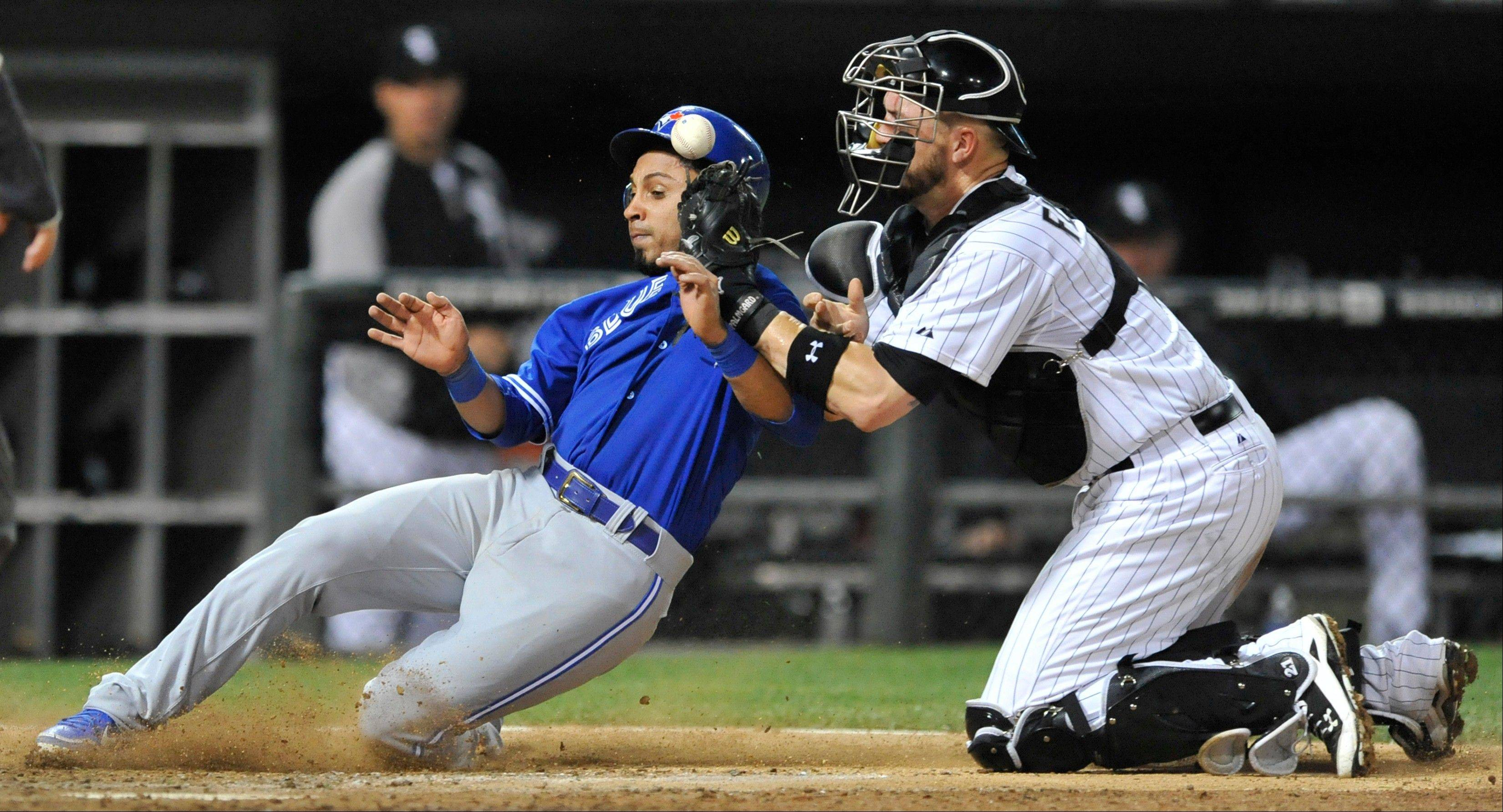 Toronto Blue Jays' Maicer Izturis scores on a Munenori Kawasaki double as Tyler Flowers tries to apply the tag during the 10th inning of the White Sox' loss to Toronto on Tuesday at U.S. Cellular Field.