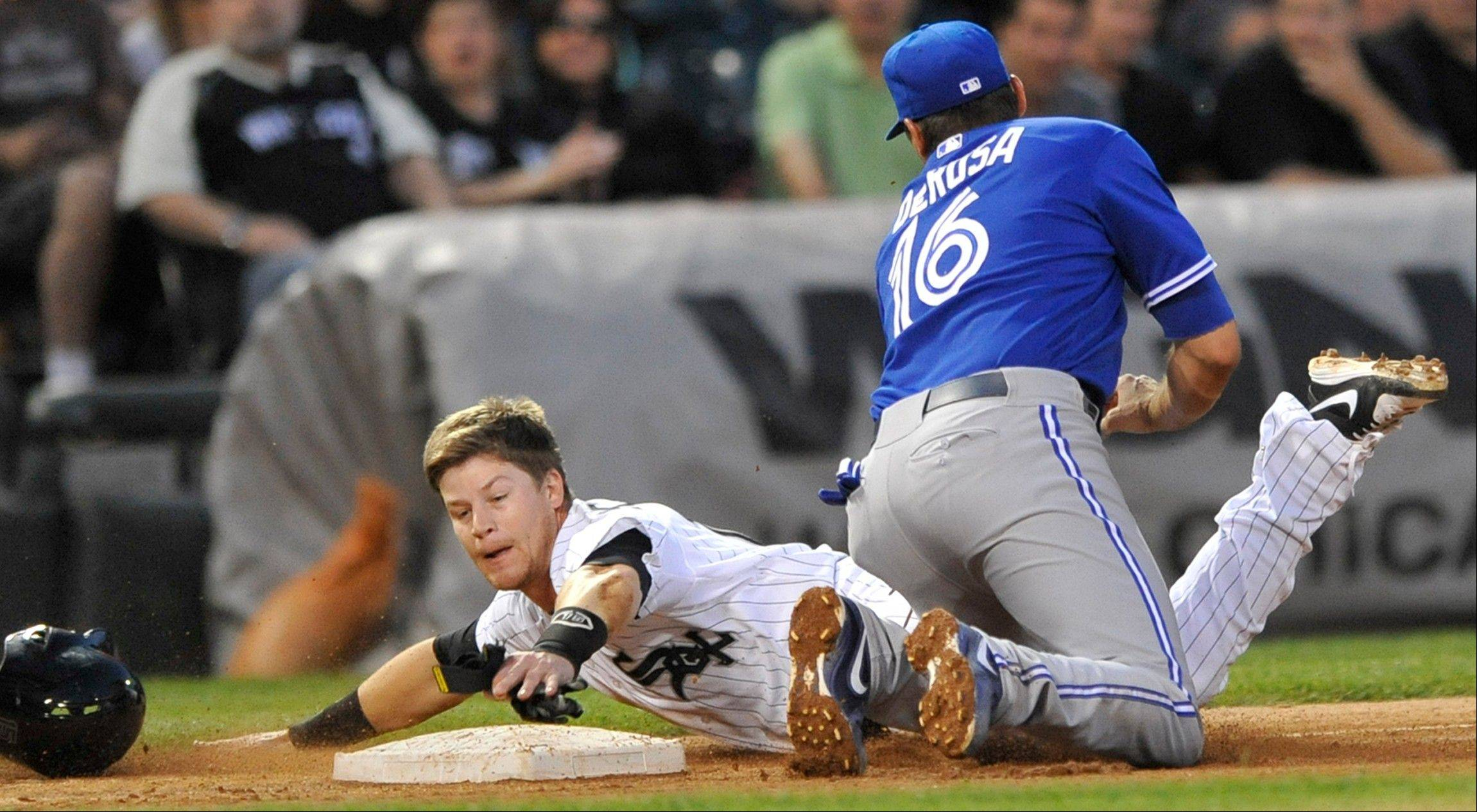 Gordon Beckham is tagged out at third base by Toronto Blue Jays third baseman Mark DeRosa (16), after Tyler Flowers singled during the fourth inning of a baseball game in Chicago, Tuesday, June 11, 2013.