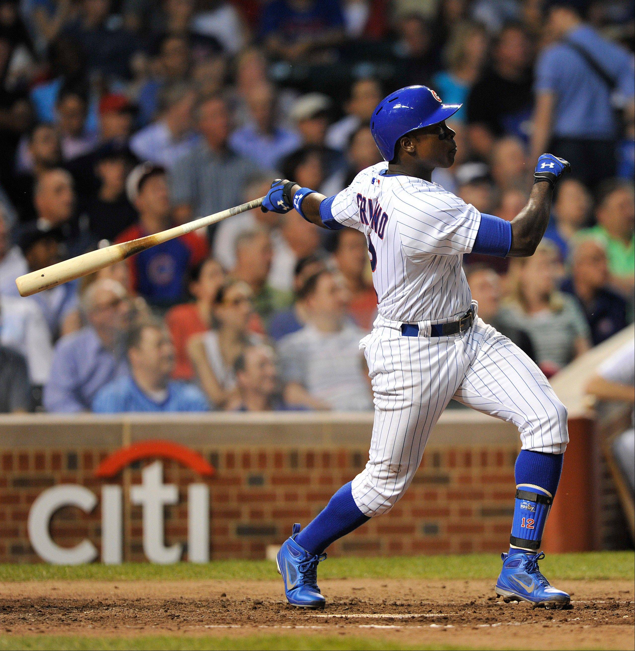 Chicago Cubs' Alfonso Soriano watches his sacrifice fly against the Cincinnati Reds during the fourth inning of a baseball game on Tuesday, June 11, 2013, in Chicago.