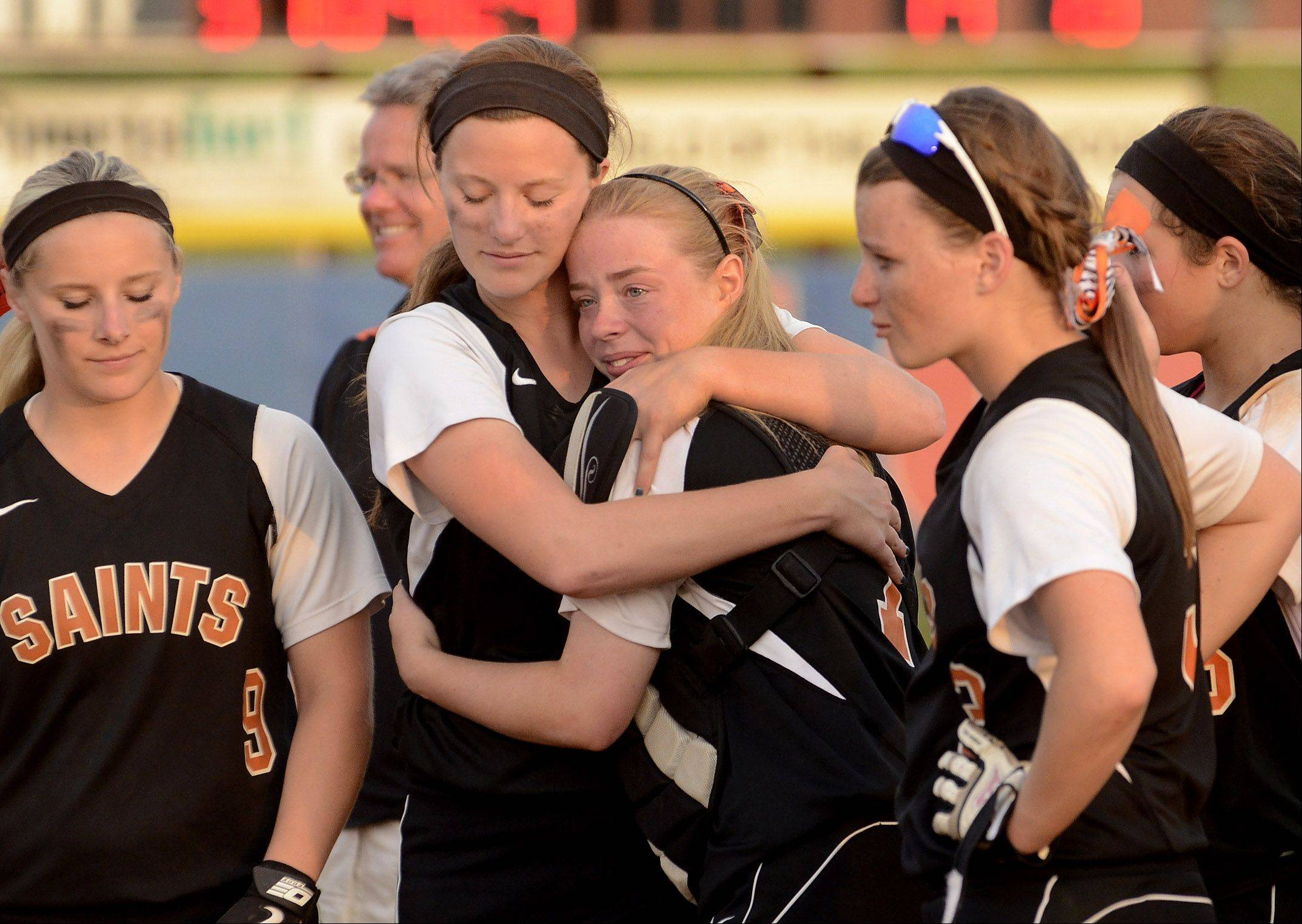 Mackenzie Lofgren, left, and Shelby Holtz console each other after losing to Minooka in Saturday's state softball tournament.