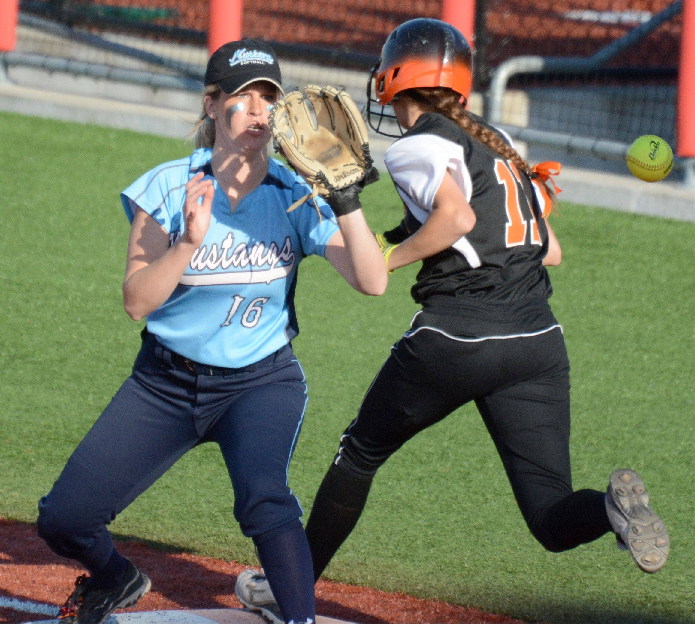 St. Charles East's Tess Hupe outruns a throw to Downers Grove South's Olivia Parks during Monday's Class 4A supersectional softball game in Rosemont.