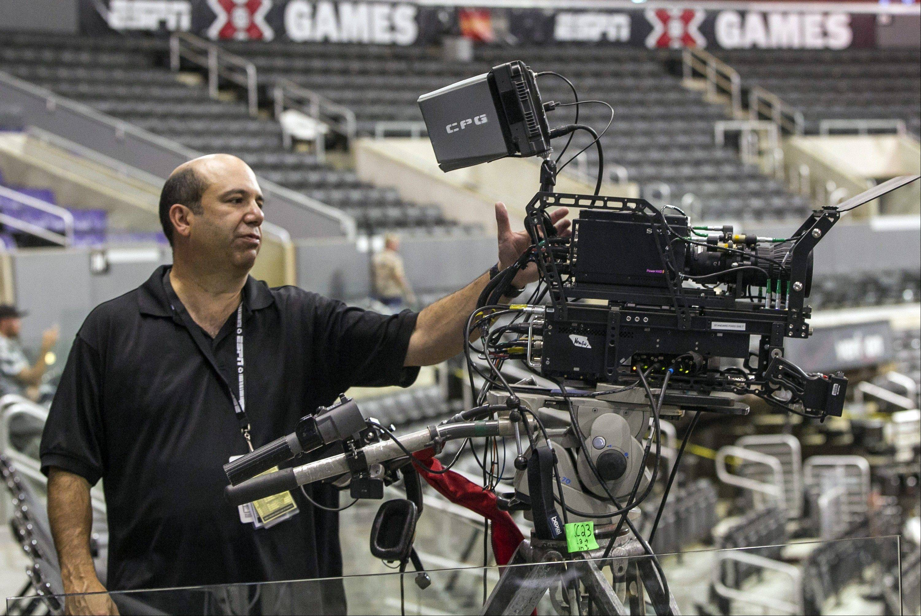 ASSOCIATED PRESS In this June 27, 2012, photo, ESPN coordinating producer Phil Orlins shows a 3-D camera set up used by ESPN 3-D Network coverage at the ESPN X-Games held at the Staples Center in Los Angeles. ESPN will stop broadcasting in 3-D by the end of the year, the network said Wednesday.