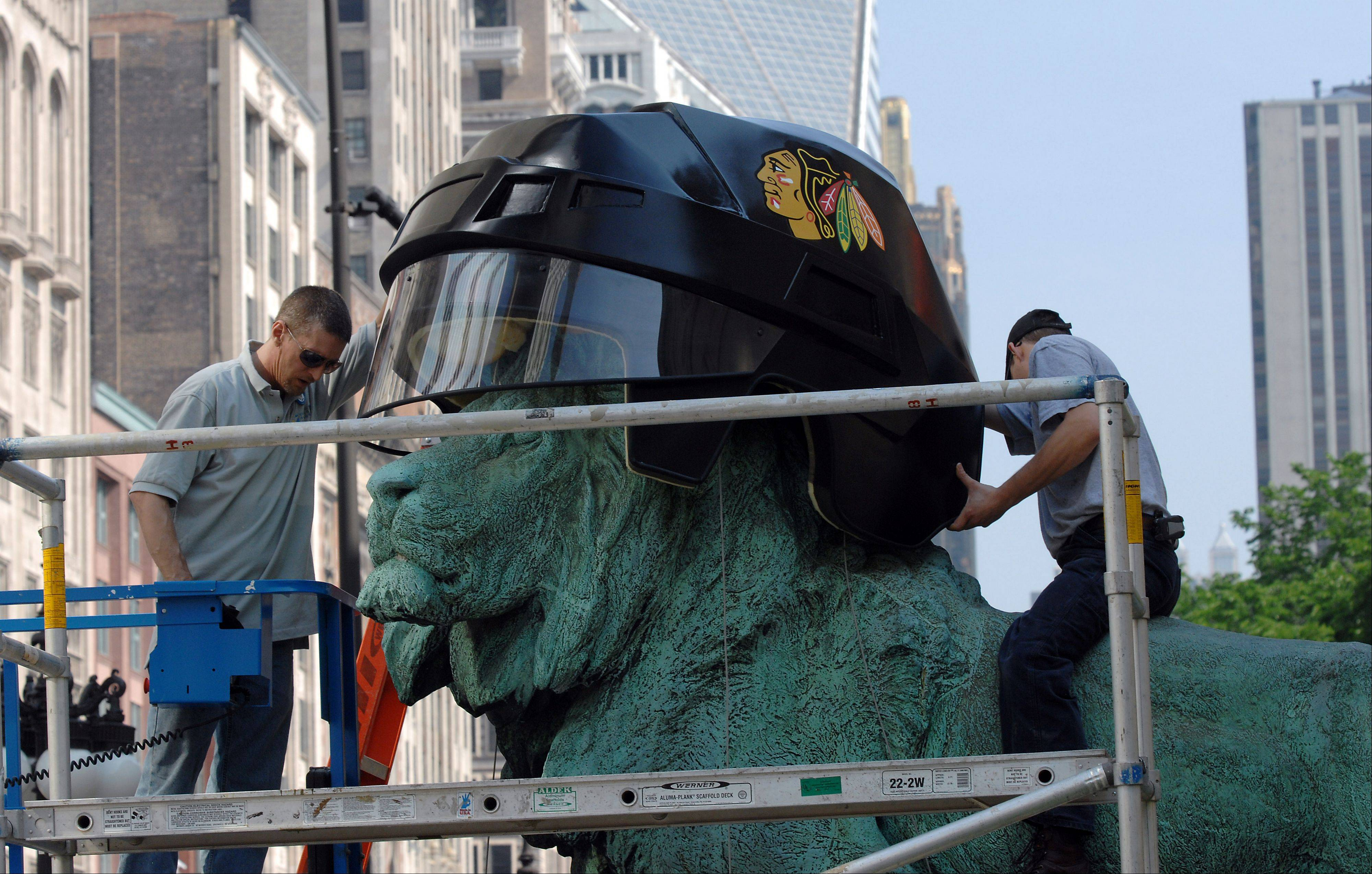 Workers fit the South lion called �standing in an attitude of defiance� with an oversized Chicago Blackhawks helmet before the teams 2010 Stanley Cup victory.