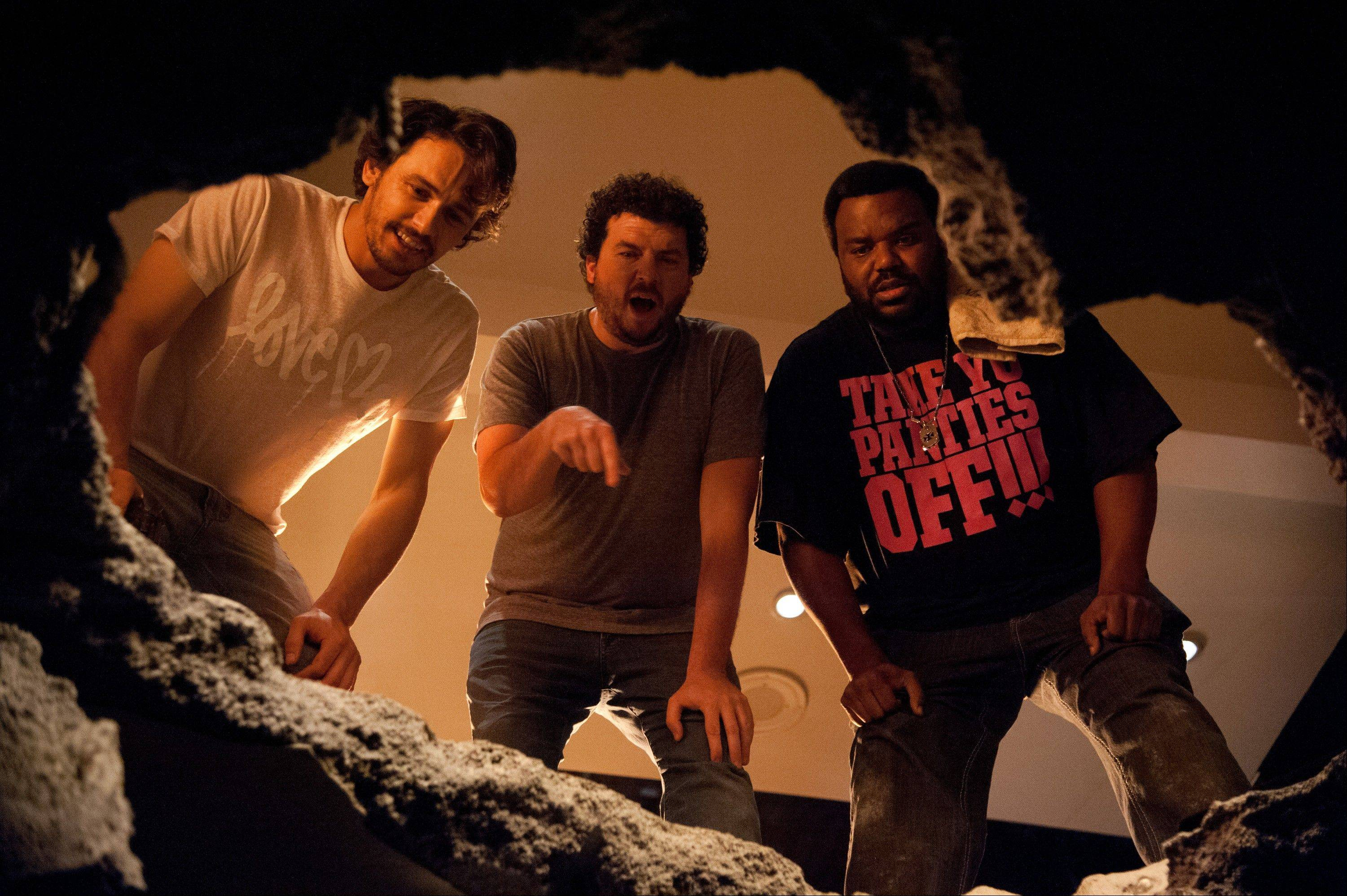 "James Franco, Danny McBride and Craig Robinson wonder what's down in the basement in the Armageddon horror comedy ""This Is The End."""
