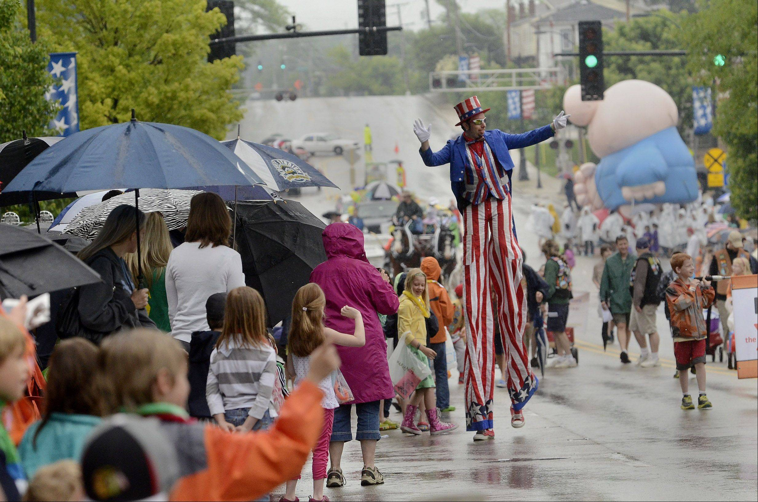 Tall Man Uncle Sam Jason Kollum waves to wet onlookers at Libertyville Days Parade on Saturday. Libertyville Days continues Sunday.