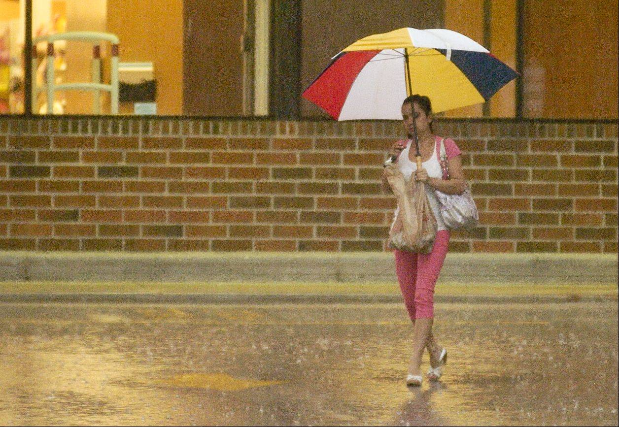 A woman uses an umbrella to keep dry as she exits the Jewel store in Wheaton during the hight of the rain, Wednesday afternoon.