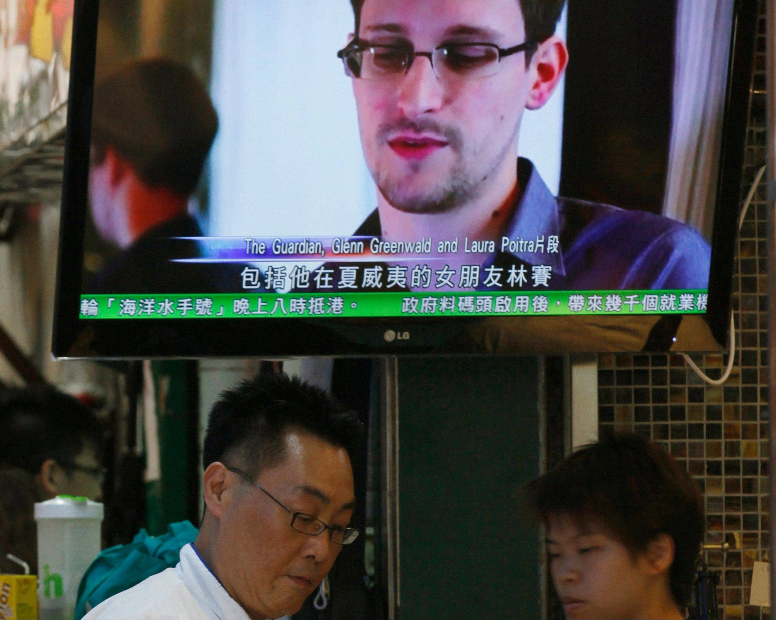 A TV screen shows a news report on Edward Snowden, a former CIA employee who leaked top-secret documents about sweeping U.S. surveillance programs, at a restaurant in Hong Kong Wednesday, June 12, 2013. Snowden dropped out of sight after checking out of a Hong Kong hotel on Monday.