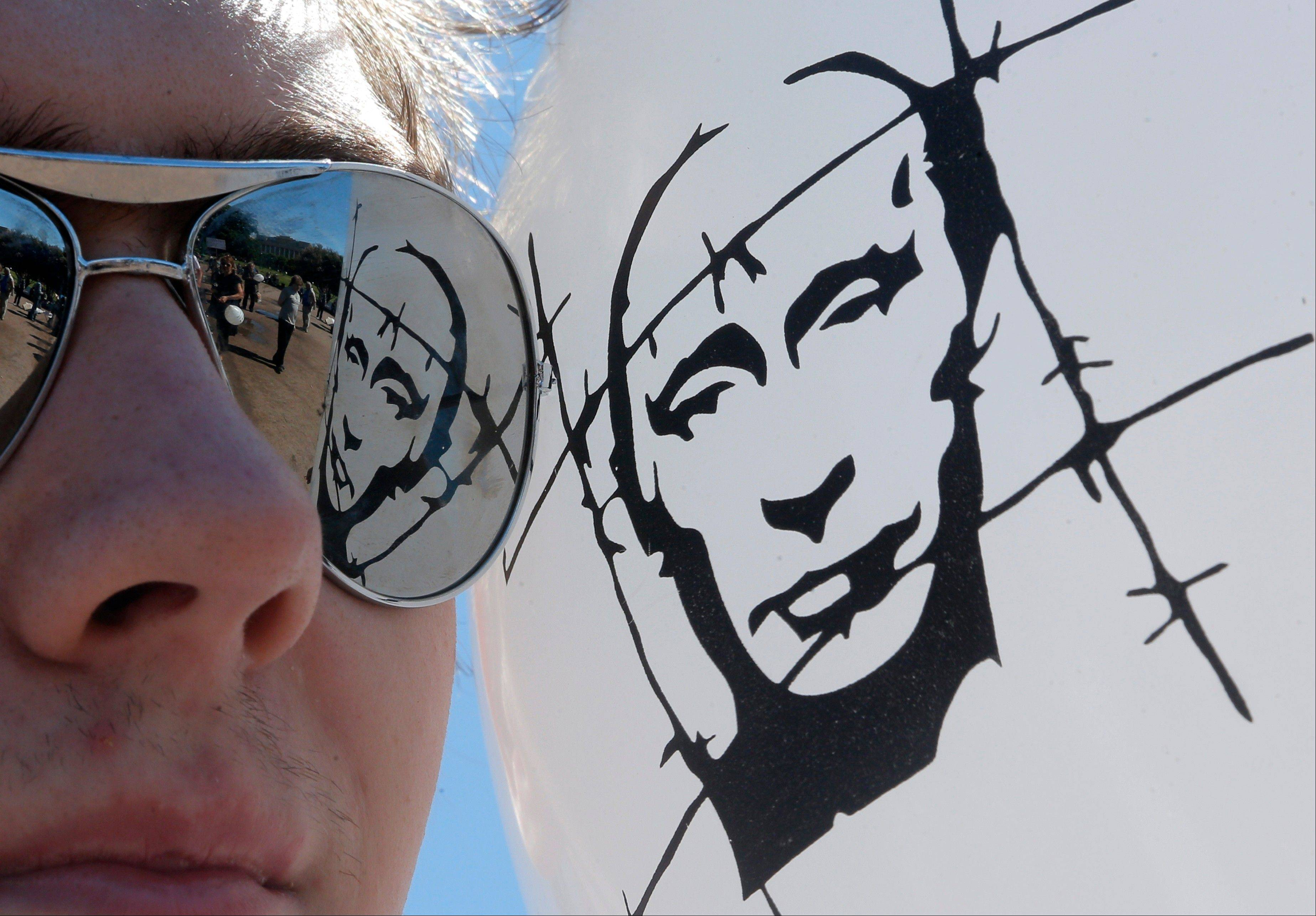 A balloon depicting Russian President Vladimir Putin behind barbed wire, reflects in glasses of an opposition protester during a protest rally in St. Petersburg, Russia, Wednesday, June 12, 2013. Wednesday's rally is in support of 27 people who face charges related to a protest that turned violent on the eve of Putin's inauguration more than a year ago.