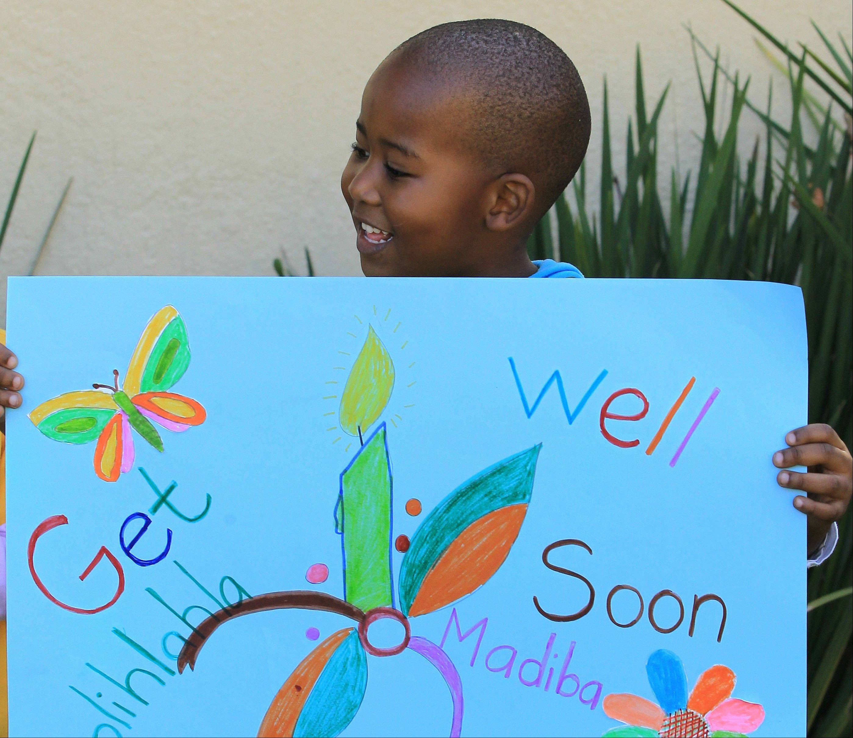 A young boy from Othandweni Community Center holds a placard wishing former South African President Nelson Mandela a prompt recovery outside his residence in Johannesburg, South Africa, Wednesday, June 12, 2013. Mandela, remains in hospital for a fifth day. The 94-year-old icon was hospitalized on Saturday for a recurring lung infection.