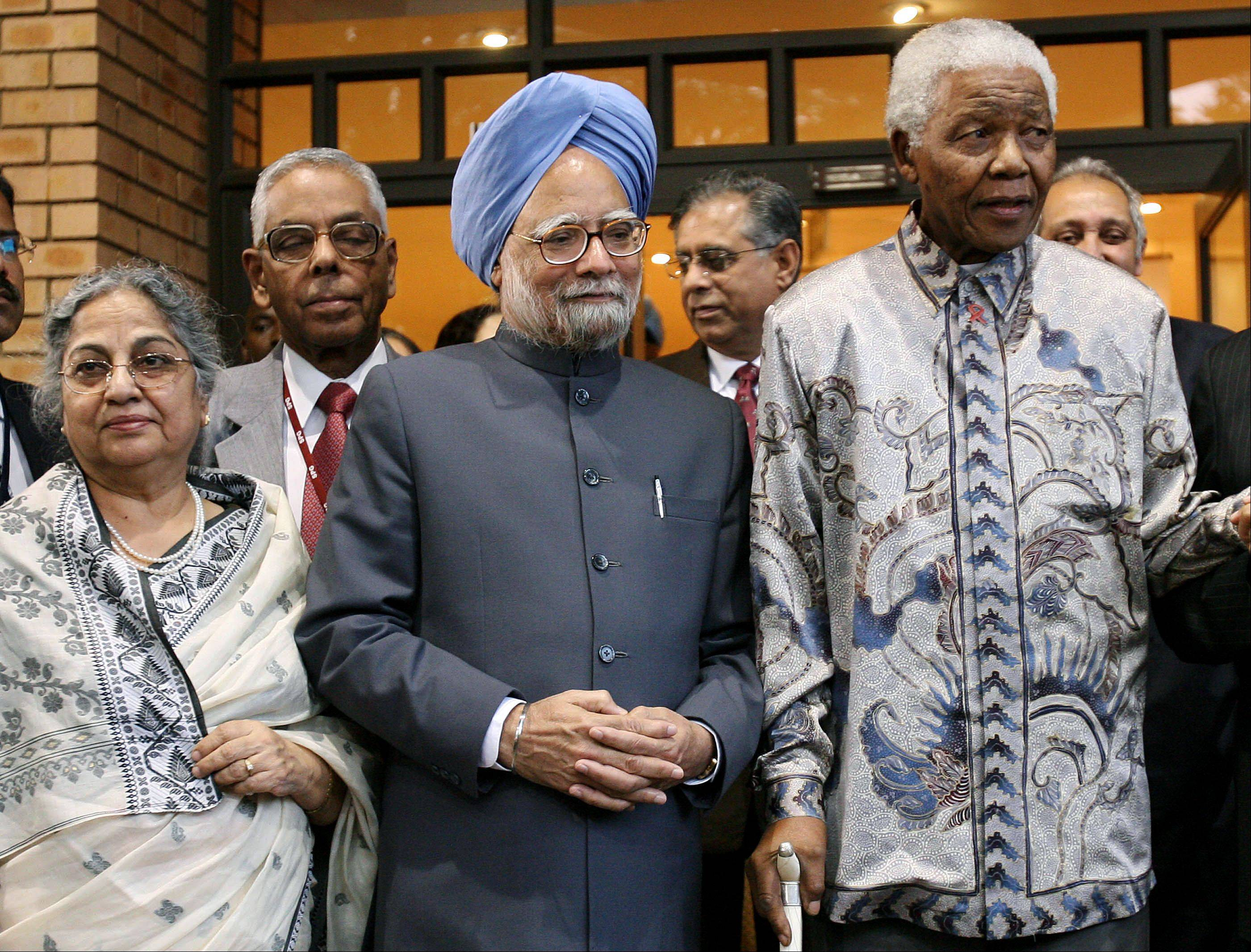 Indian Prime Minister Manmohan Singh, center, and his wife Kaur, left, pose for photographers with former South African president Nelson Mandela after their meeting at the Mandela foundation in Johannesburg Monday Oct. 2, 2006.