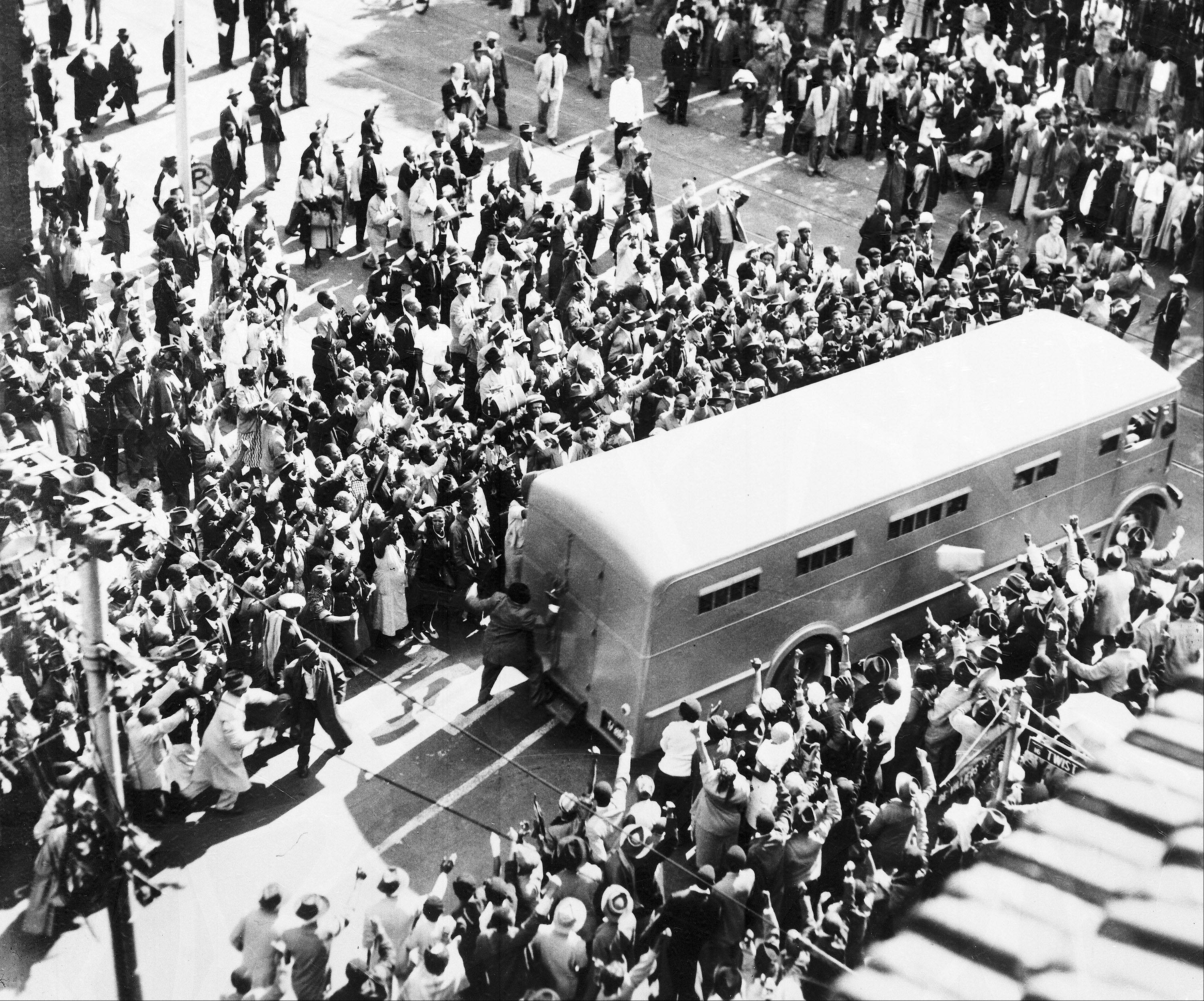 Crowds cheer as a police van brings prisoners to the Drill Hall, in Johannesburg, South Africa, Dec. 31, 1956, for the start of the 'Treason Trial'. Nelson Mandela was among the people arrested and standing trial.