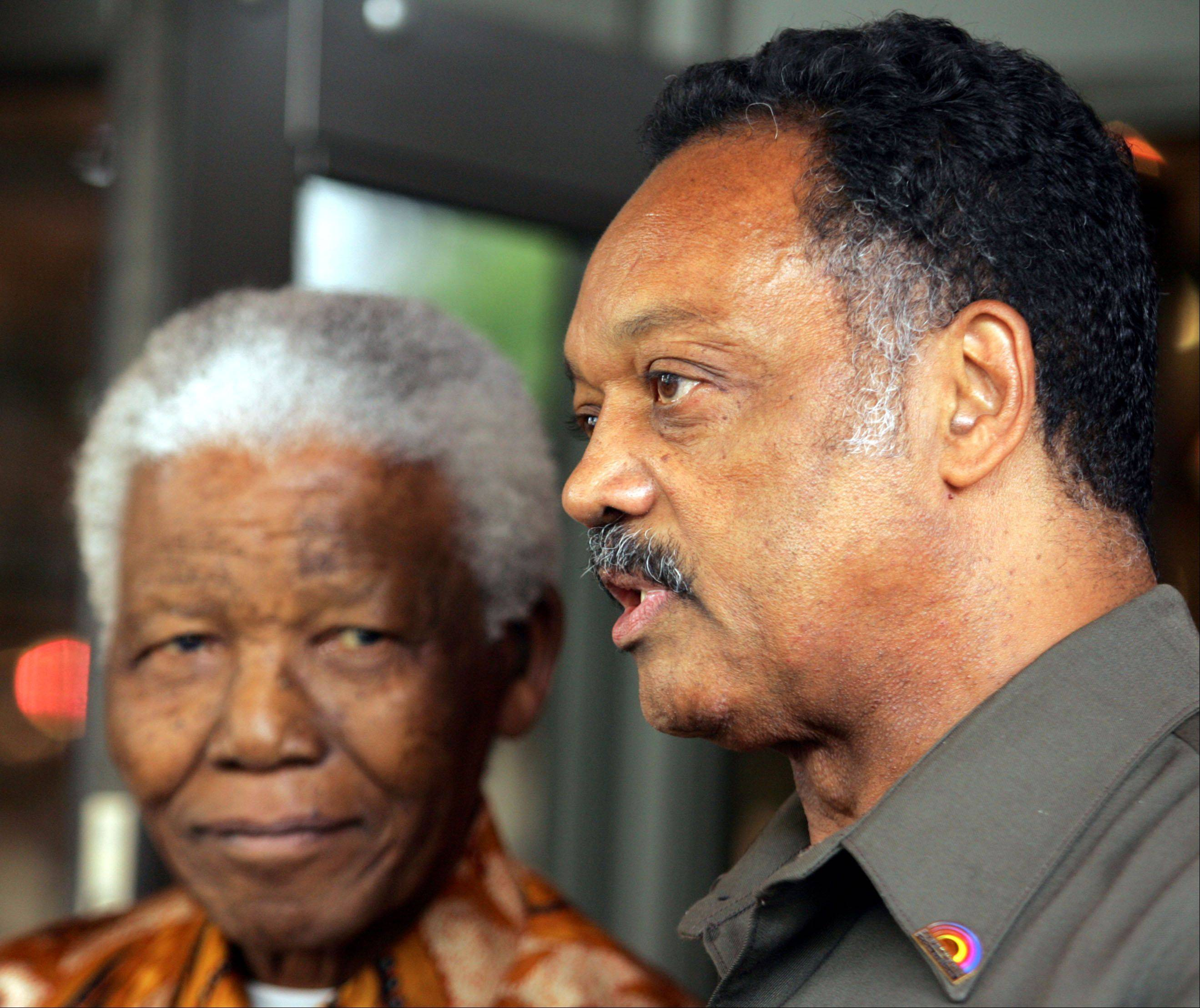 American Rev. Jesse Jackson, right, speaks to journalist as former South African president Nelson Mandela, left, looks on after their meeting in Johannesburg, South Africa, Wednesday, Oct. 26, 2005.