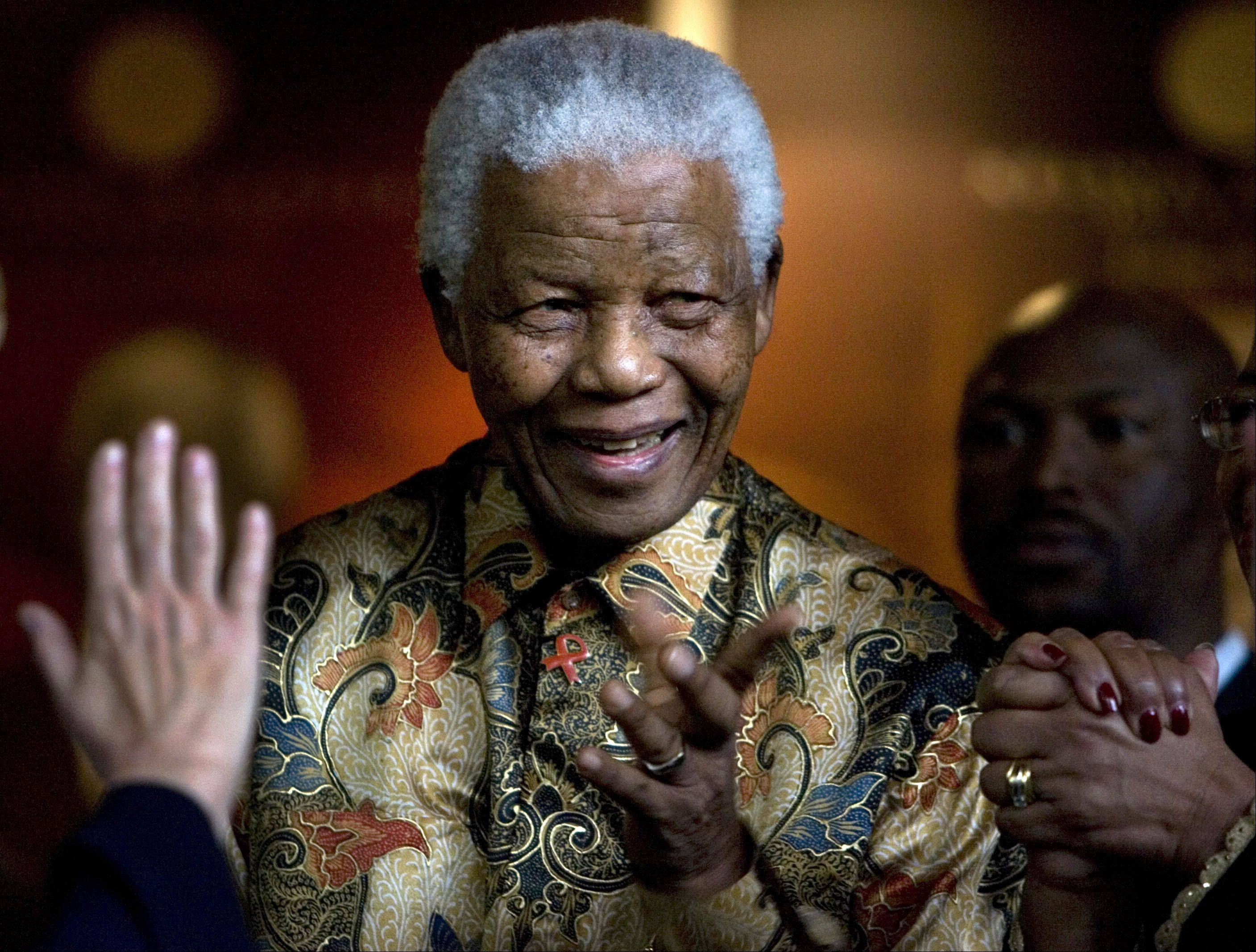In this Oct. 6, 2007 file photo, former South African President Nelson Mandela reacts as German Chancellor Angela Merkel, left, waves farewell after a meeting at the Nelson Mandela Foundation building in Johannesburg, South Africa.
