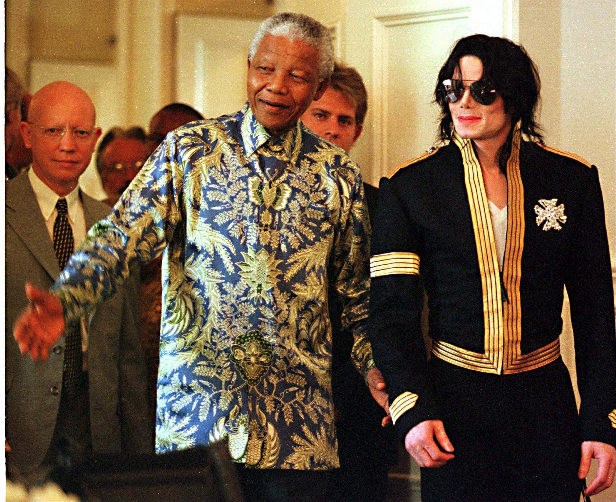 South African President Nelson Mandela, left, and American pop singer Michael Jackson arrive at a news conference in Cape Town Tuesday, March 23, 1999.