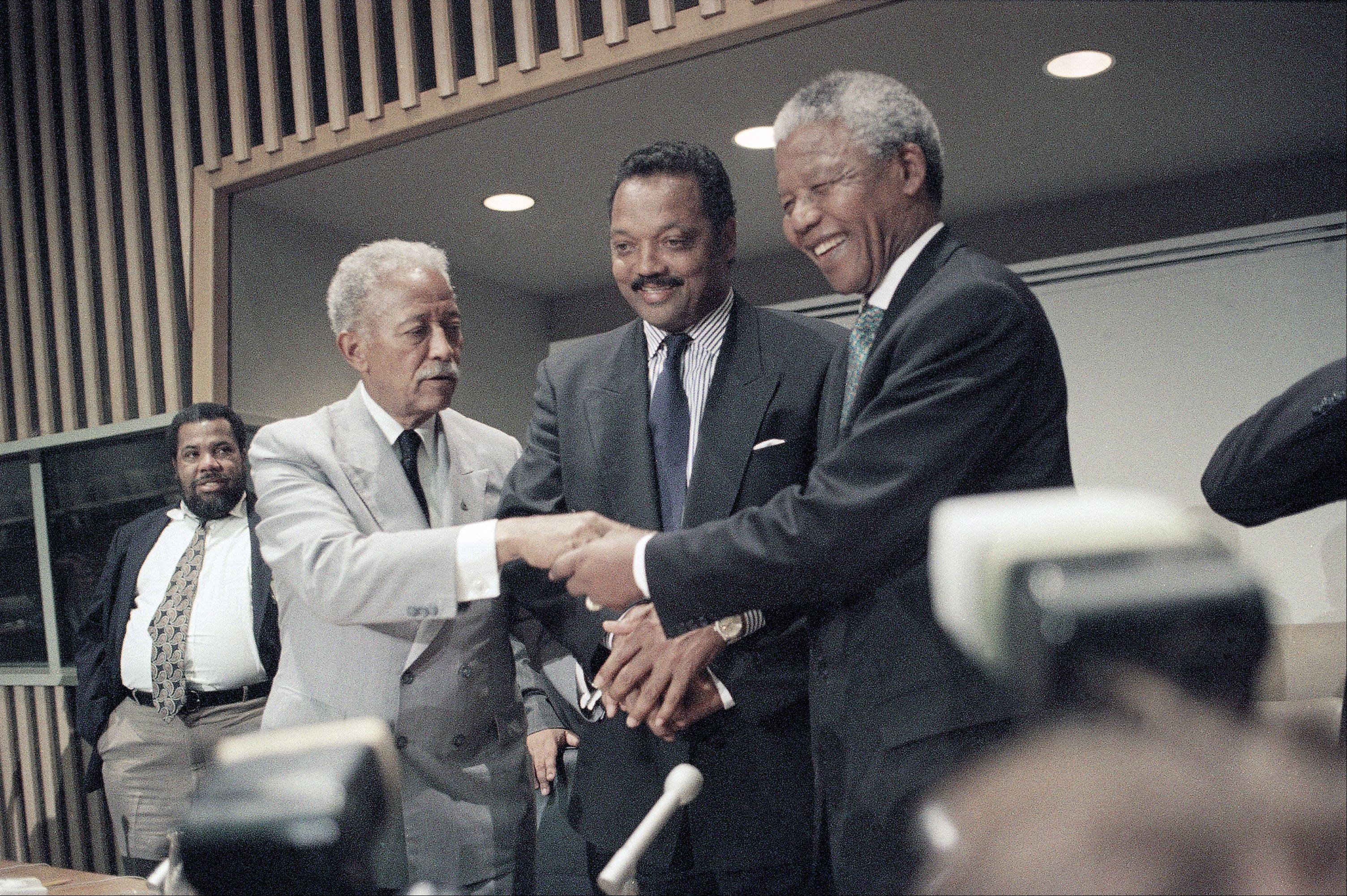 New York City Mayor David Dinkins, left, and the Rev. Jesse Jackson, center, joins hands with African National Congress President Nelson Mandela Friday, Sept. 24, 1993 in New York, following a press conference at the United Nations.