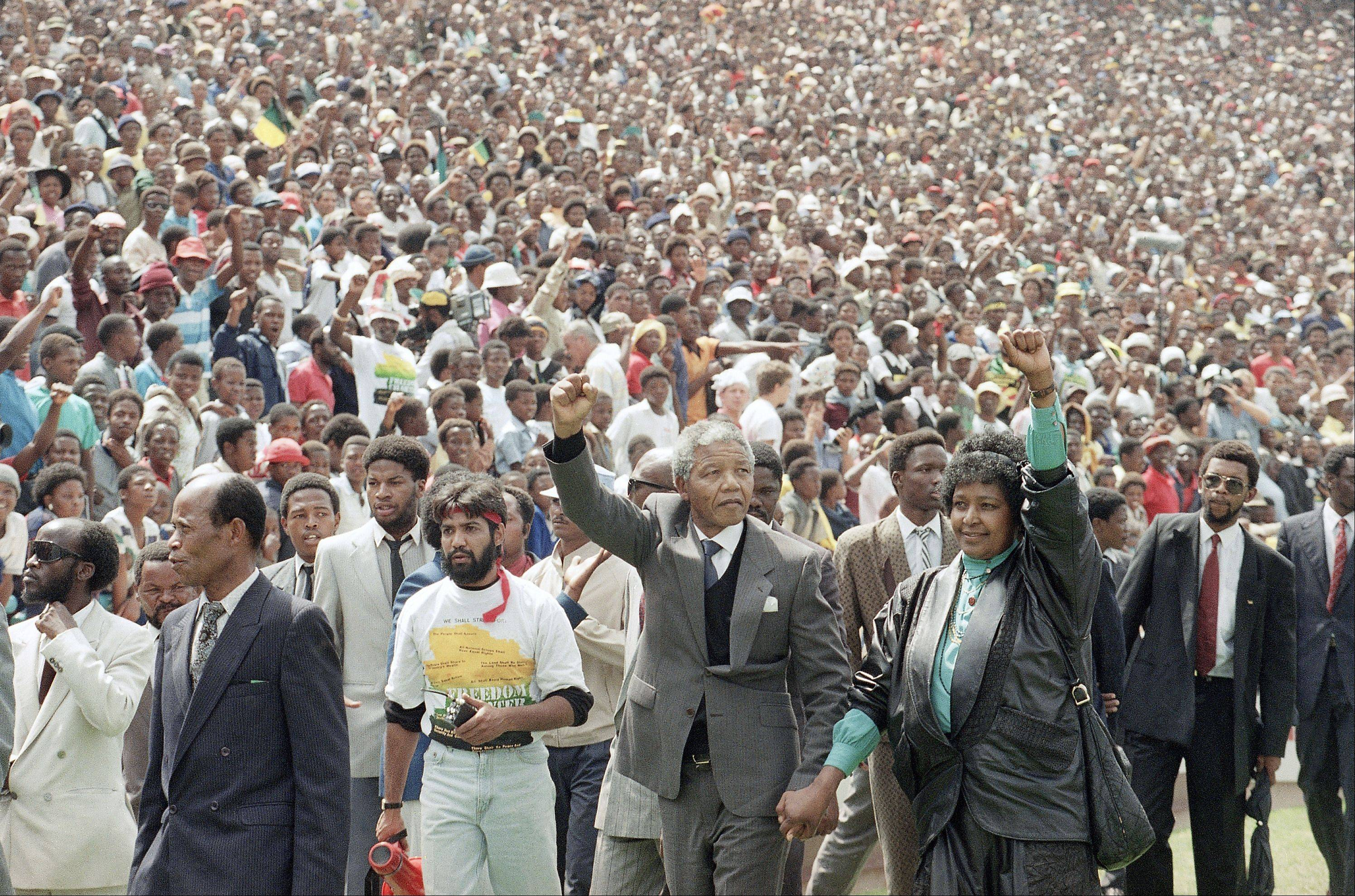 Nelson Mandela and Winnie Mandela give back power salutes as they enter Soweto's Soccer City stadium, South Africa Tuesday, Feb. 13, 1990. 120,000 thousand people packed the venue to hear his speech.