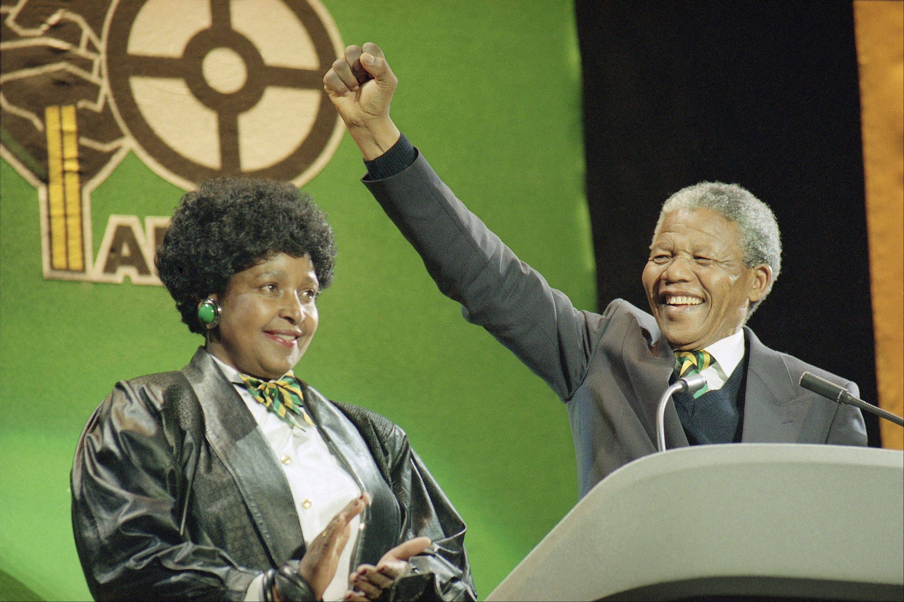 South African anti-apartheid leader Nelson Mandela with his wife Winnie at his side, raises his fist as he acknowledges the cheers of thousands at a rock concert Monday, April 16, 1990 at London's Wembley Stadium.