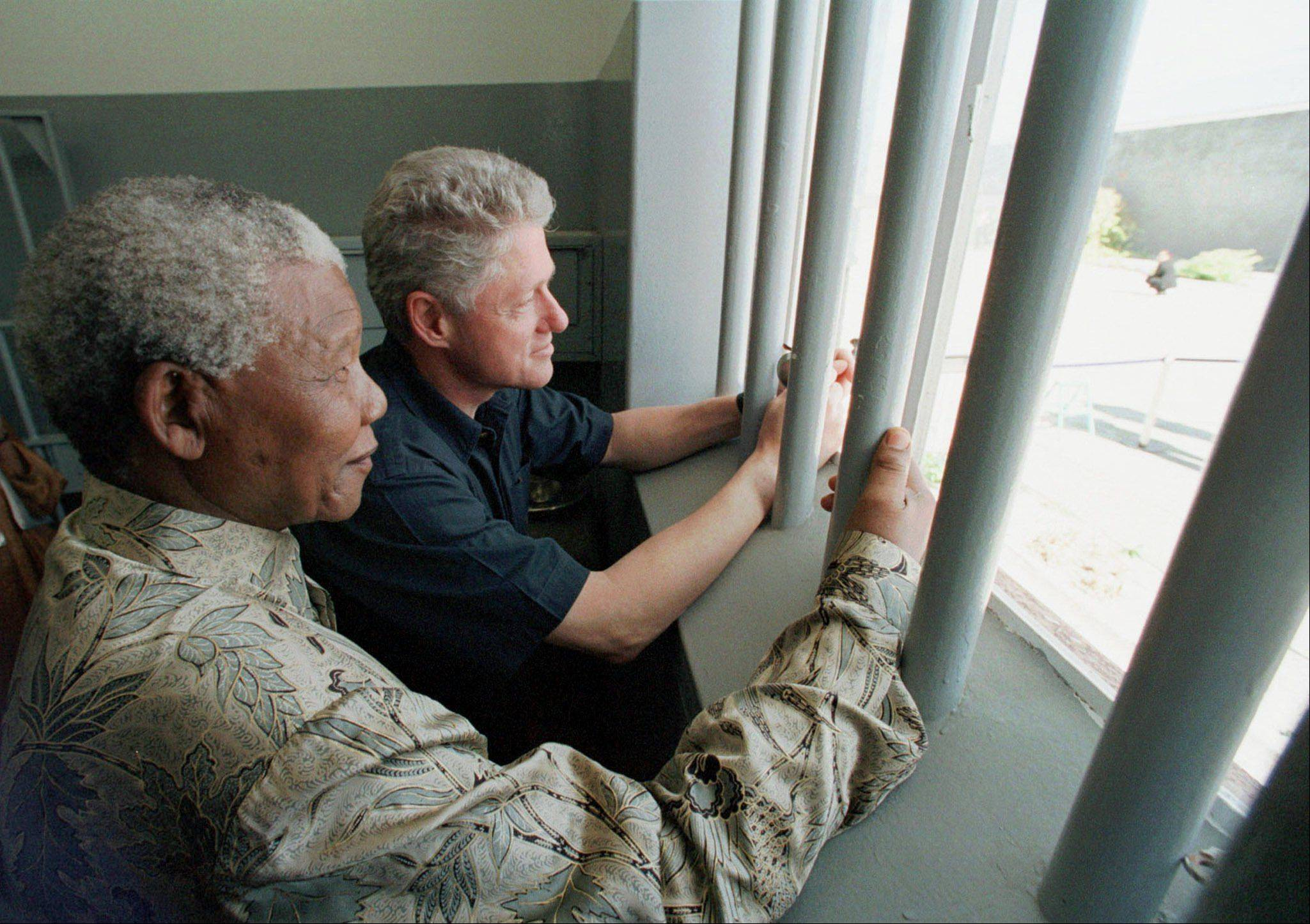 South African President Nelson Mandela, foreground, and U.S. President Bill Clinton peer out from Section B, prison cell No. 5, on Robben Island, South Africa March 27, 1998. Mandela spent 18 years of his 27-year prison term on the island.