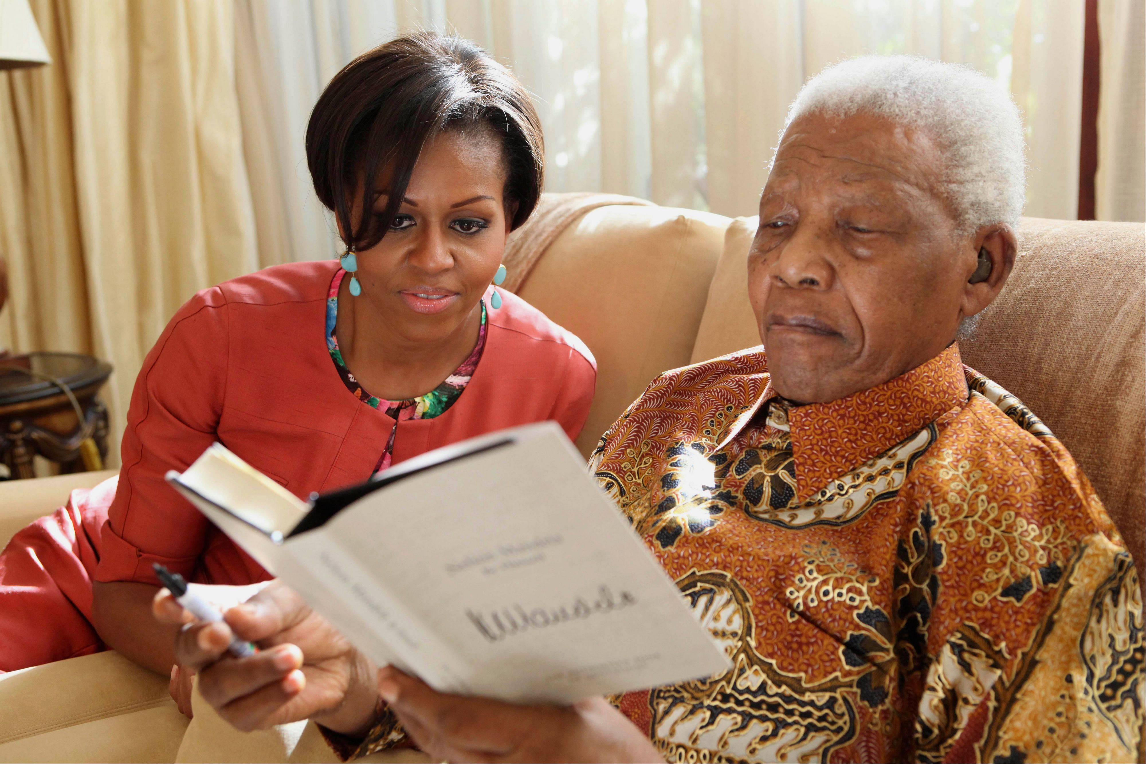 In this photo provided by the Nelson Mandela Foundation on Tuesday, June 21, 2011, US First Lady Michelle Obama, left, with former South African President Nelson Mandela, at this home, in Houghton, South Africa.