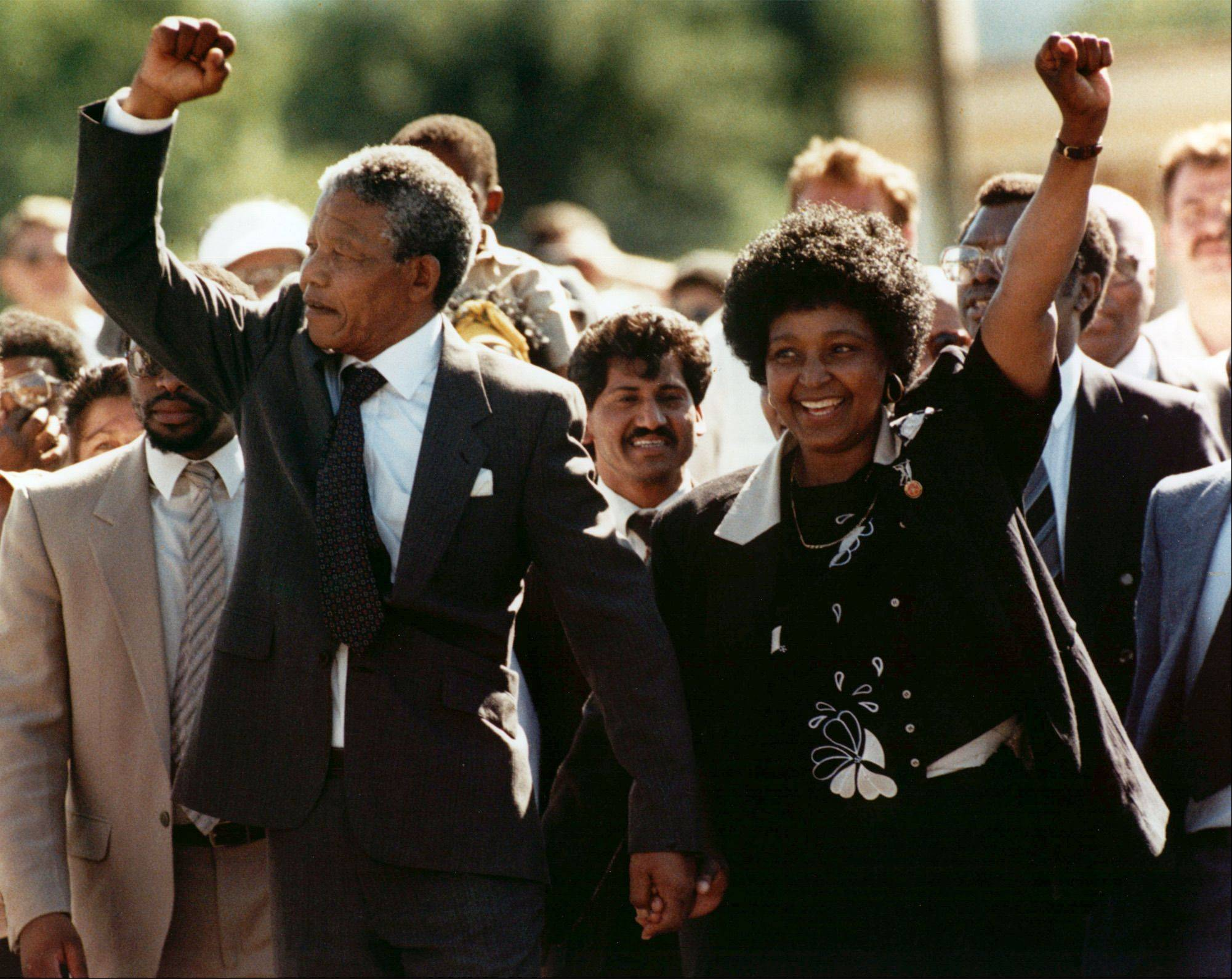 Nelson Mandela and wife Winnie, walking hand in hand, raise clenched fists upon his release from Victor prison, Cape Town, Feb. 11, 1990.