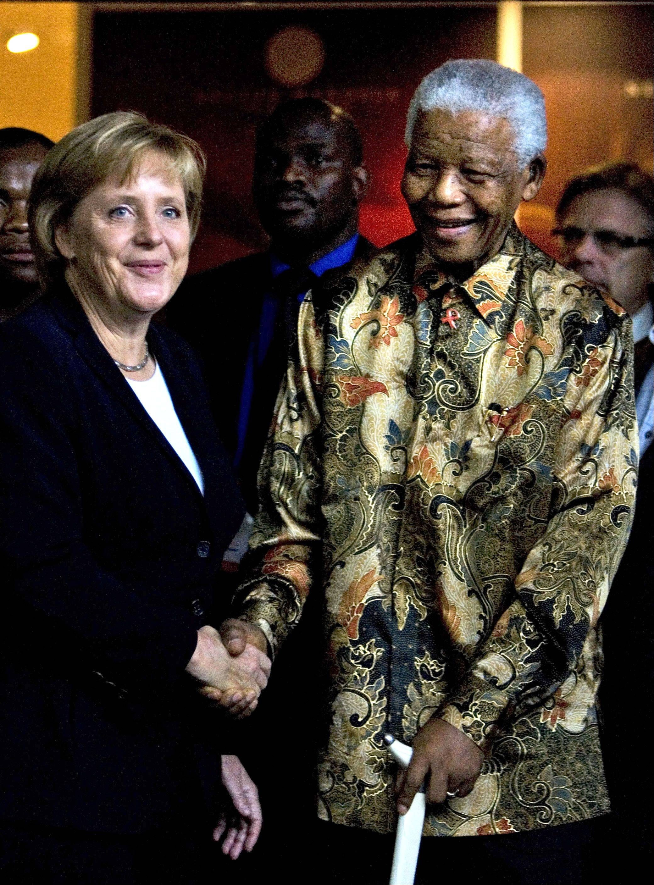 German Chancellor Angela Merkel, left, and former South African President Nelson Mandela shake hands at the Nelson Mandela Foundation building in Johannesburg, South Africa, Oct. 6, 2007.