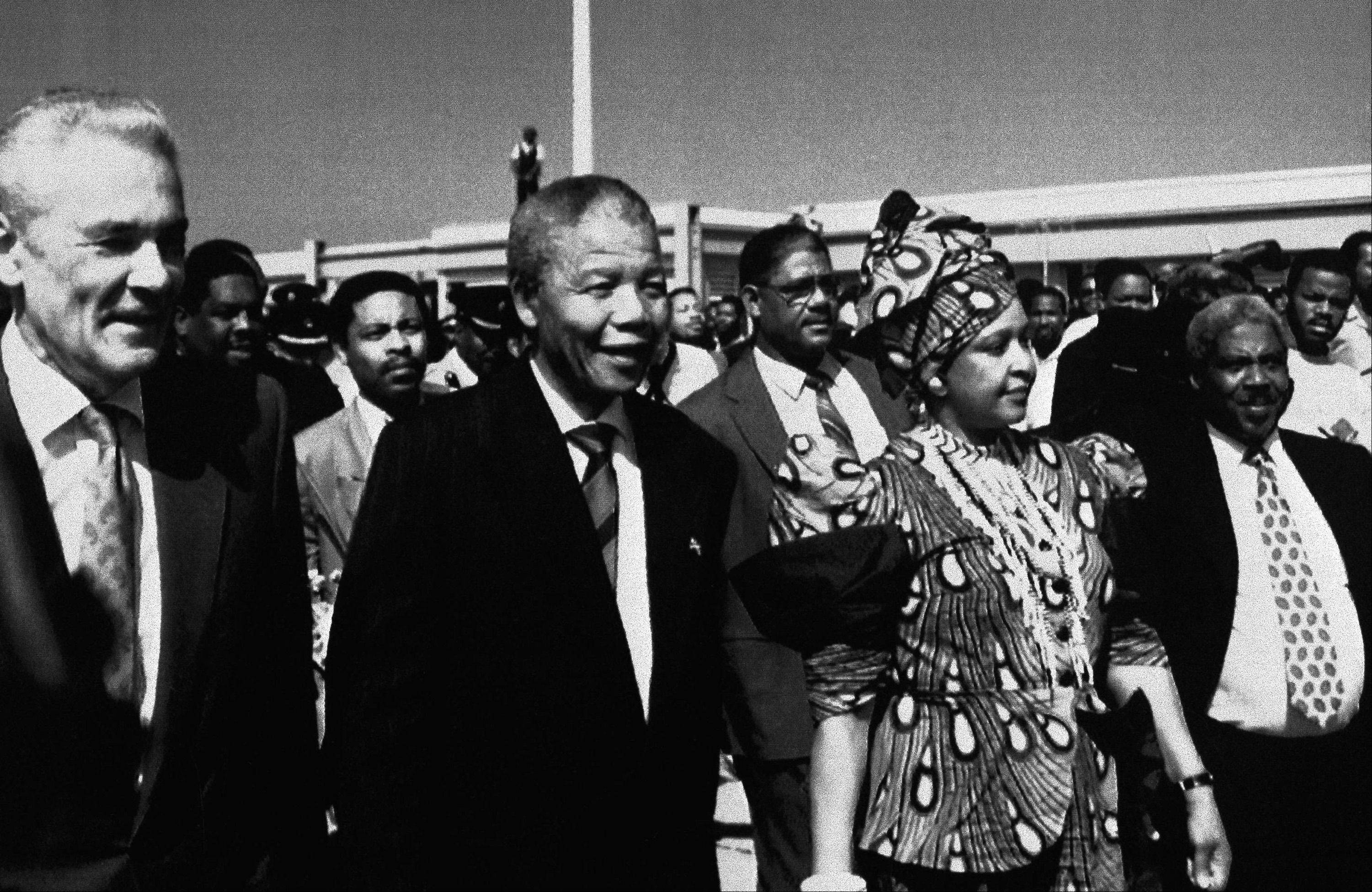 Nelson Mandela, second from left, and his wife Winnie, are escorted by Jamaican Prime Minister Michael Manley, left, after their arrival at Norman Manley International Airport, July 24, 1991, Kingston, Jamaica.