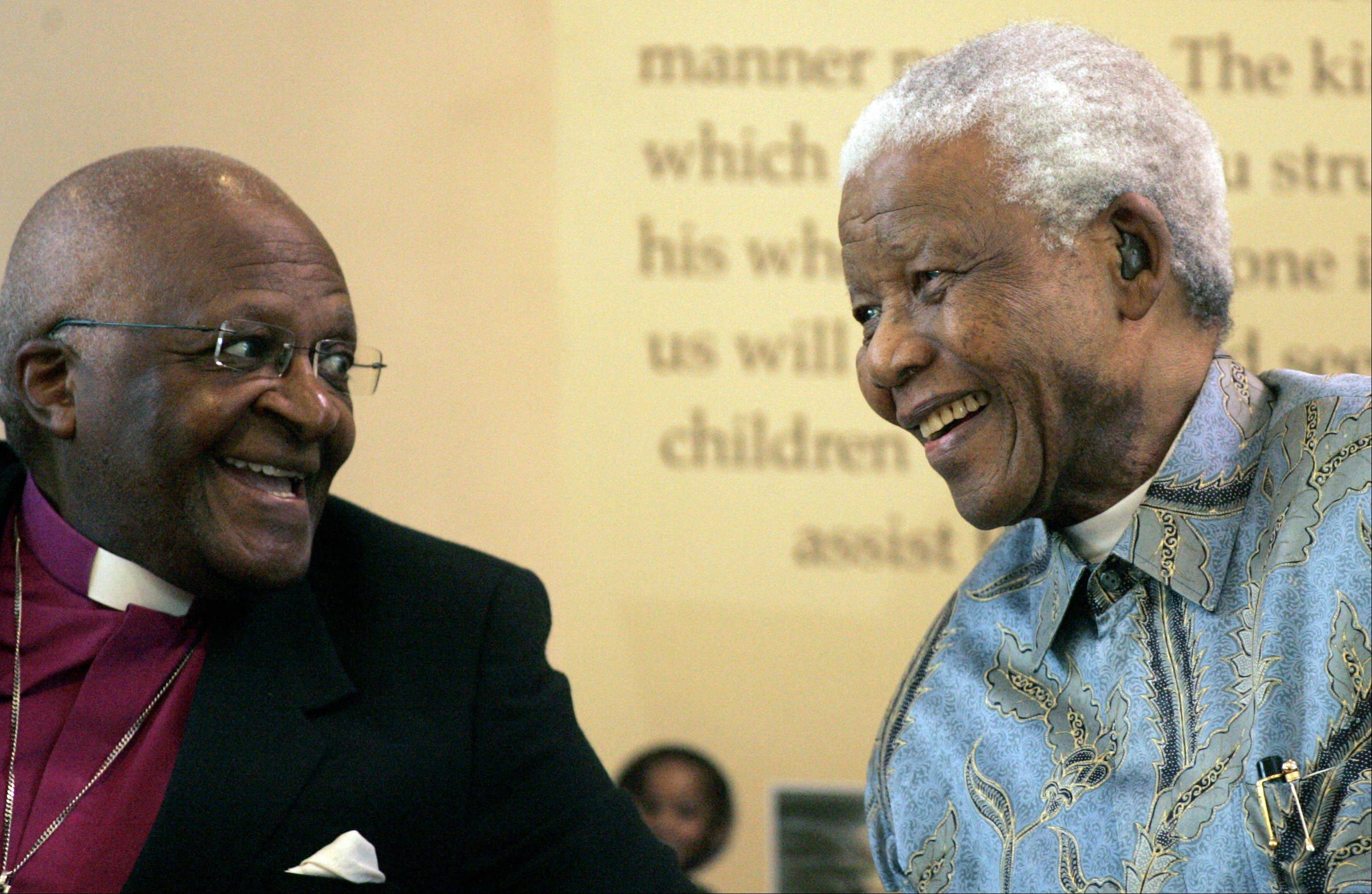 Former South African President Nelson Mandela, right, reacts with Archbishop Desmond Tutu, during the launch of a Walter and Albertina Sisulu exhibition, called, 'Parenting a Nation,' at the Nelson Mandela Foundation in Johannesburg, South Africa, March 12, 2008.