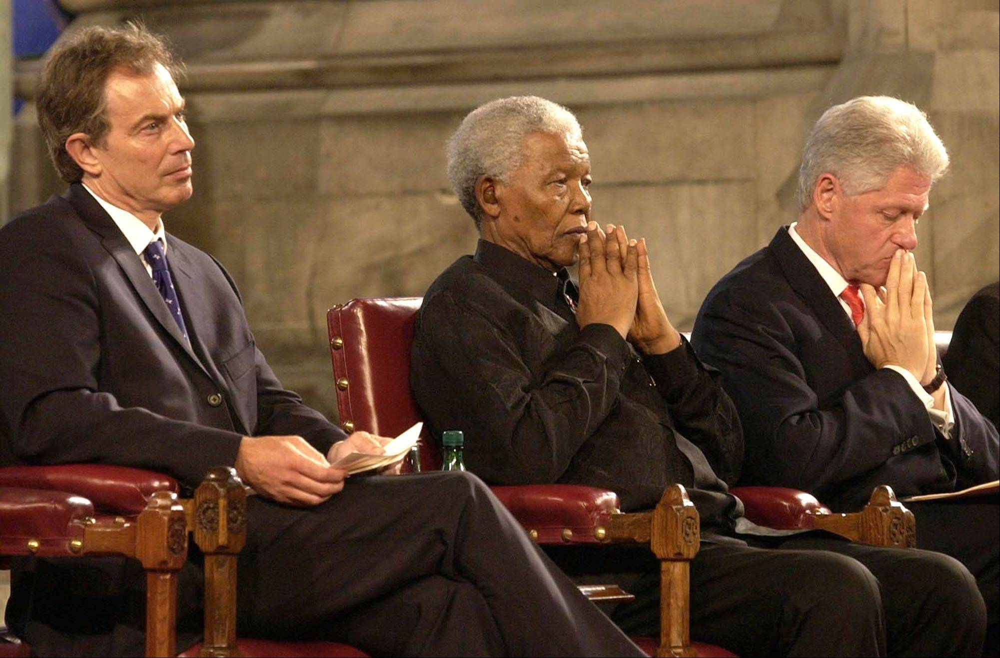 British Prime Minister Tony Blair, left, former South African President Nelson Mandela, center, and former US President Bill Clinton pause during a gala night to mark the centenary of the Rhodes Trust and the establishment of the Mandela Rhodes Foundation, at Westminster Hall, London, July 2, 2003.
