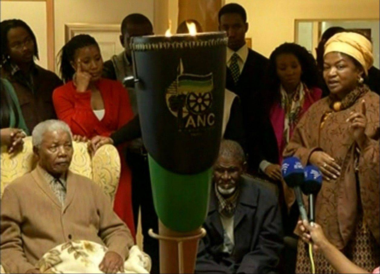 This video image taken from SABC television shows Nelson Mandela, left, receiving a torch to celebrate the African National Congress' centenary from ANC chairperson Baleka Mbete, right, in Mandela's home village Qunu May 30, 2012.