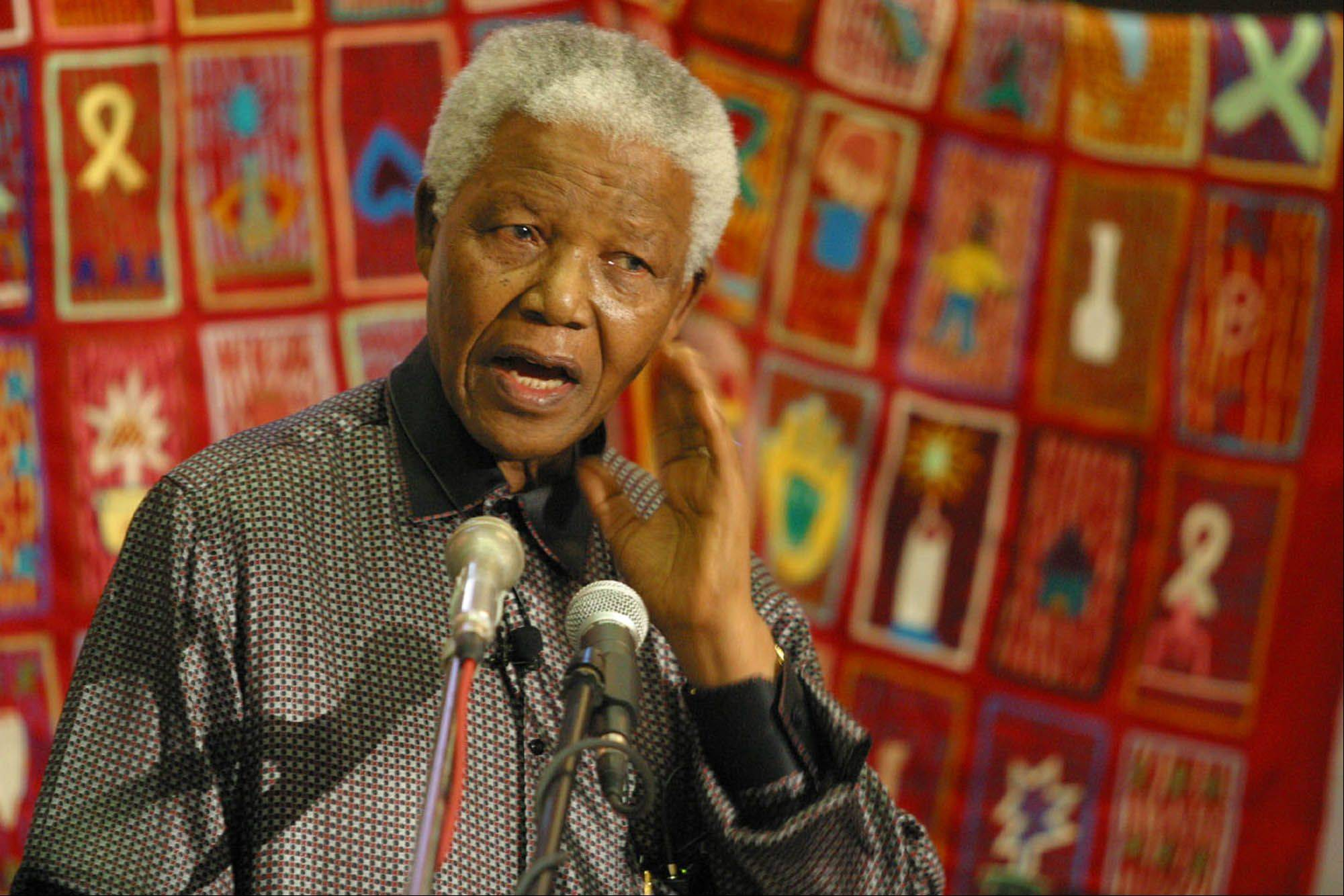 Former South African President Nelson Mandela stands before an AIDS quilt during a World AIDS Day function in Bloemfontein, South Africa, Sunday Dec. 1, 2002.
