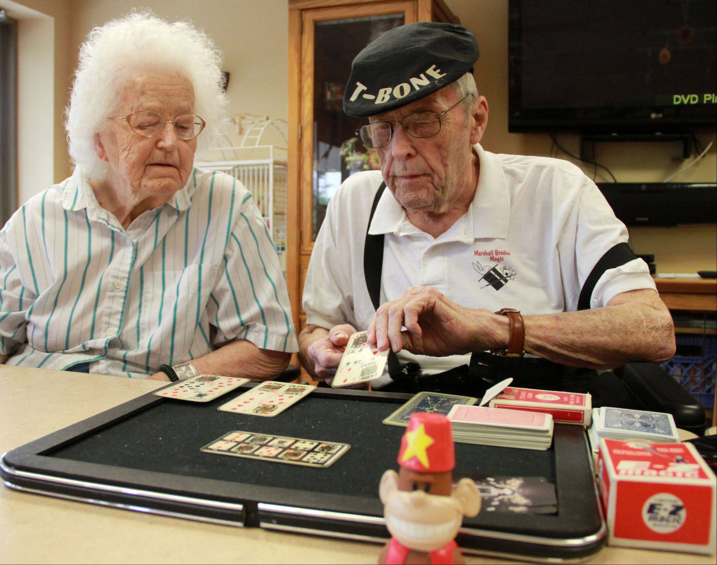 "Don Theobald, 85, the magician clown who regularly appeared on ""Bozo's Circus"" doing ""T-Bone's Magic Circus,"" shows Jeannette Breslin a card trick while teaching a magic class at Victory Centre of River Woods, the assisted living facility where he lives, in Melrose Park."