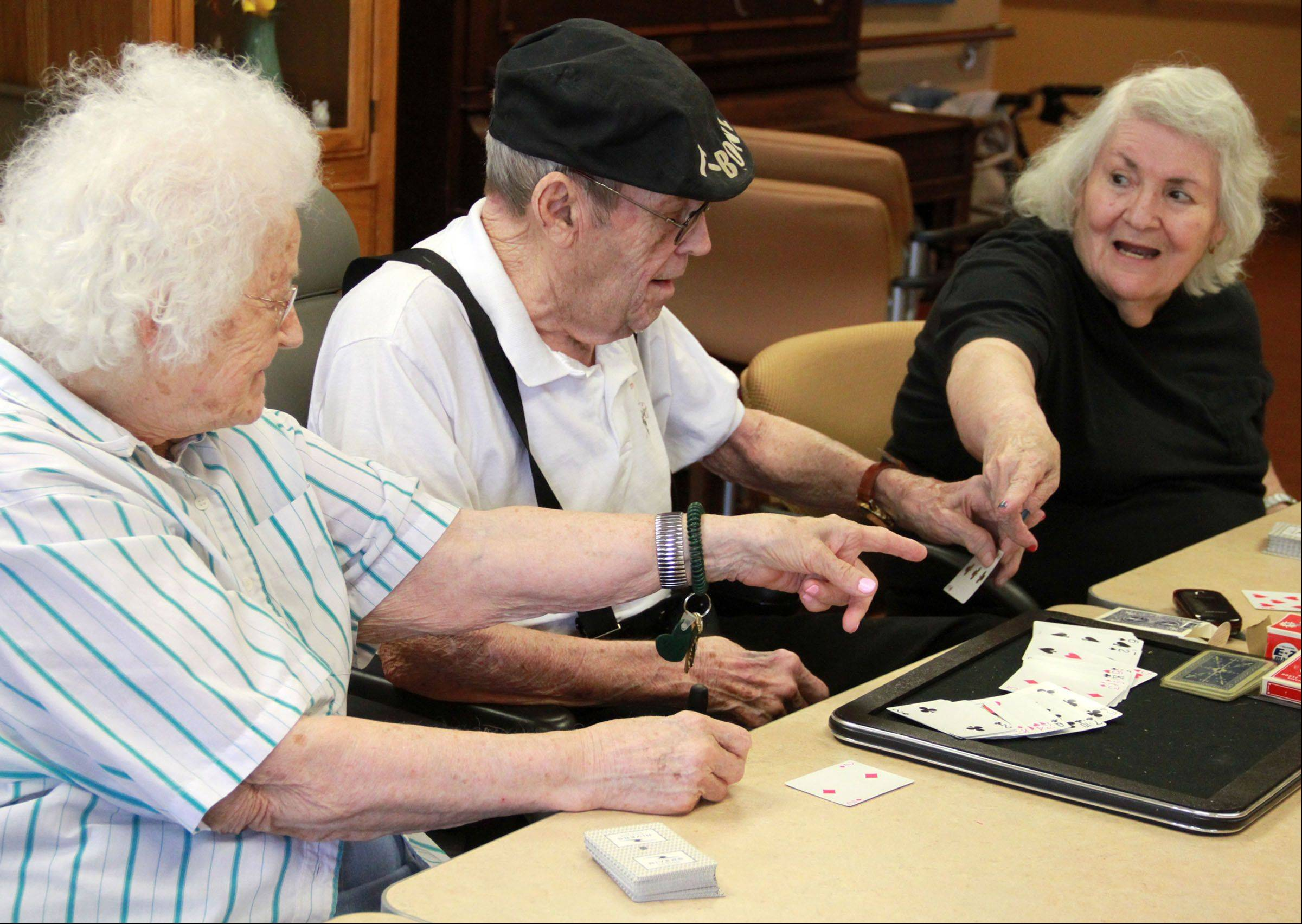 Don Theobald asks Jeannette Breslin, left, and Josie Flores to figure out a card trick while teaching a magic class at Victory Centre of River Woods, the assisted living facility where he lives, in Melrose Park.