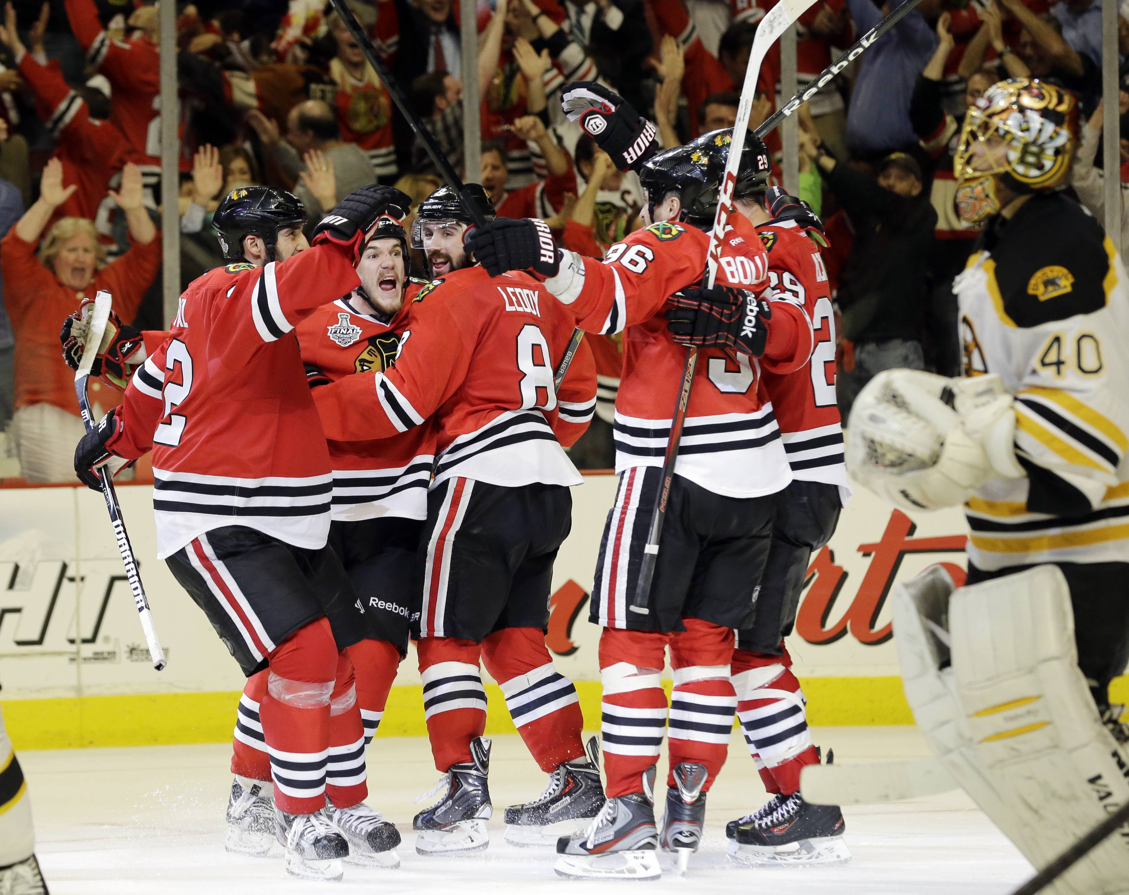 Blackhawks center Andrew Shaw, second from left, celebrates with his teammates after scoring the winning goal during the third overtime period of Game 1 in their NHL Stanley Cup Final hockey series against the Boston Bruins, Thursday, June 13, 2013, in Chicago.