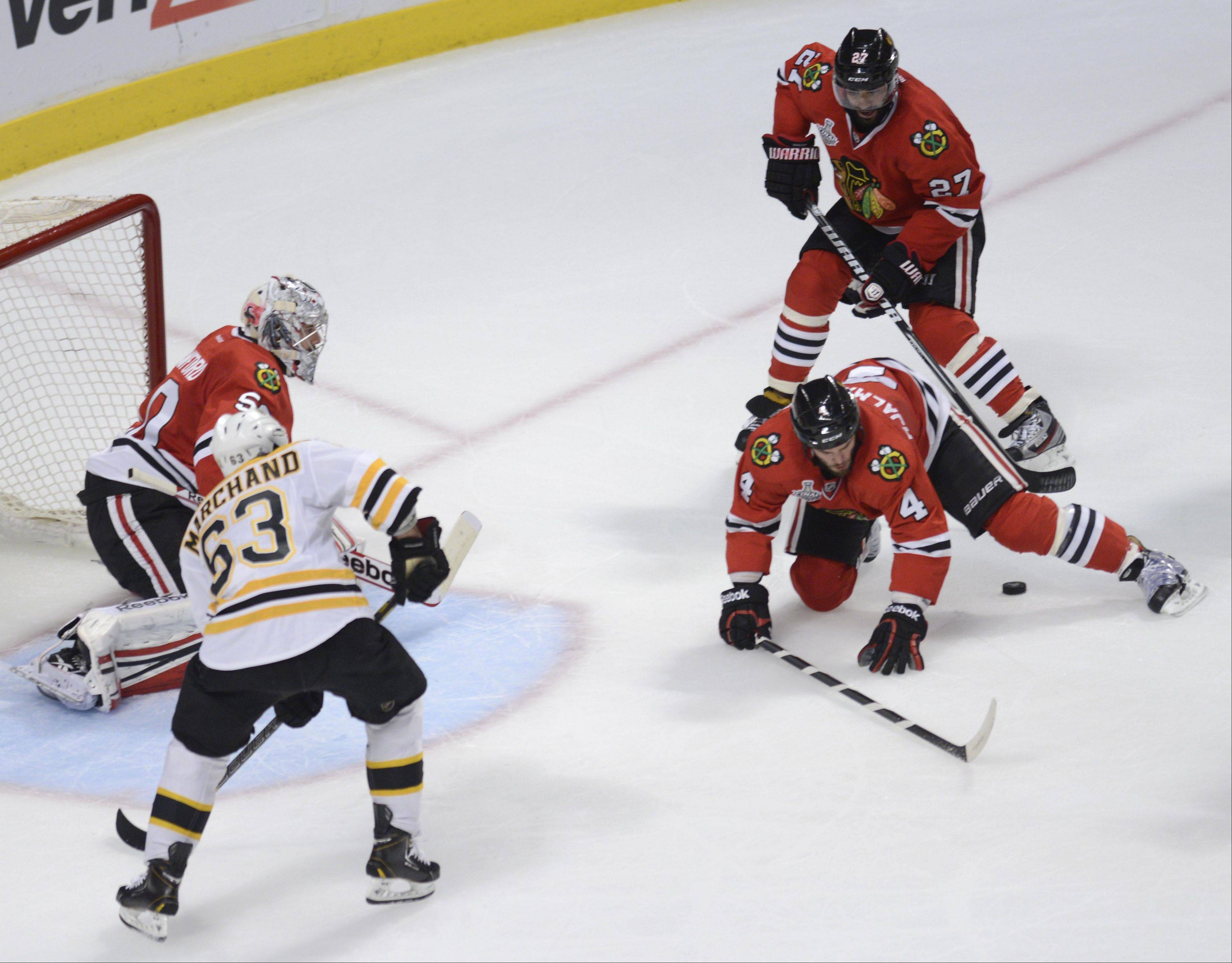 Chicago Blackhawks defenseman Niklas Hjalmarsson falls over the loose puck as Boston Bruins left wing Brad Marchand comes into position in front of the net.