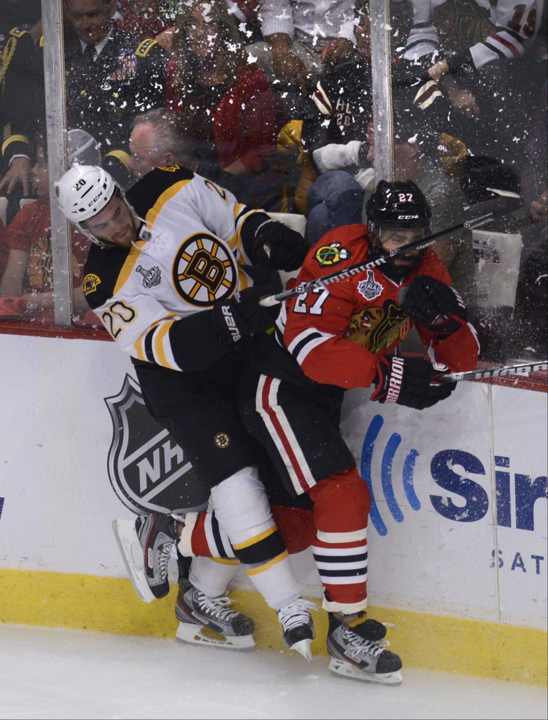 Chicago Blackhawks defenseman Johnny Oduya and Boston Bruins left wing Daniel Paille crash into the boards.