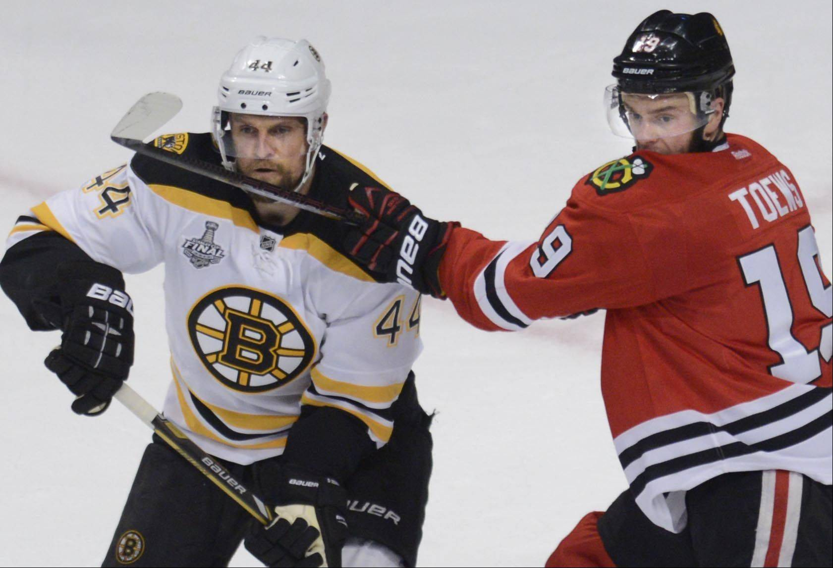 Chicago Blackhawks center Jonathan Toews battles with Boston Bruins defenseman Dennis Seidenberg in front of the net.