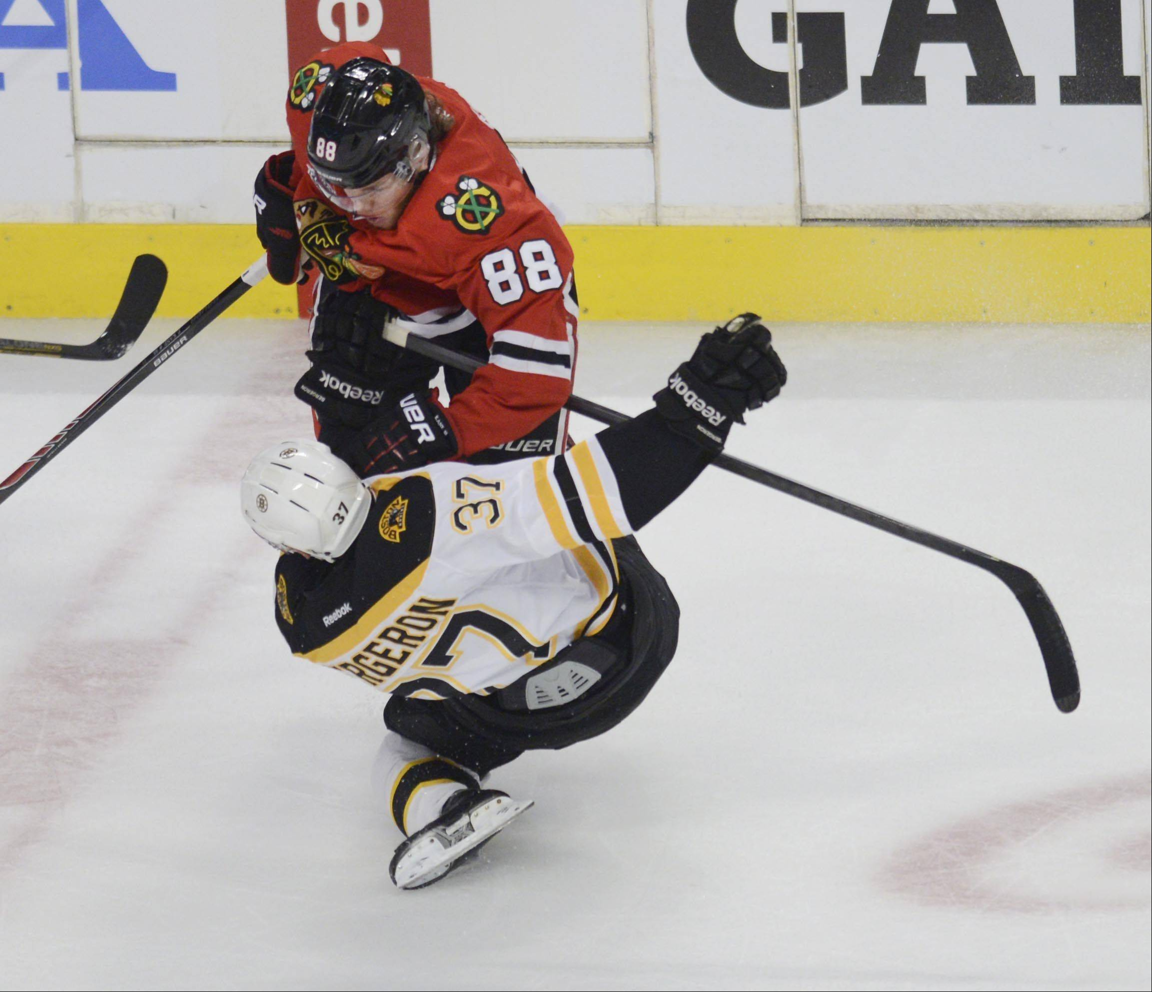 Chicago Blackhawks right wing Patrick Kane knocks Boston Bruins center Patrice Bergeron to the ice in the first period.